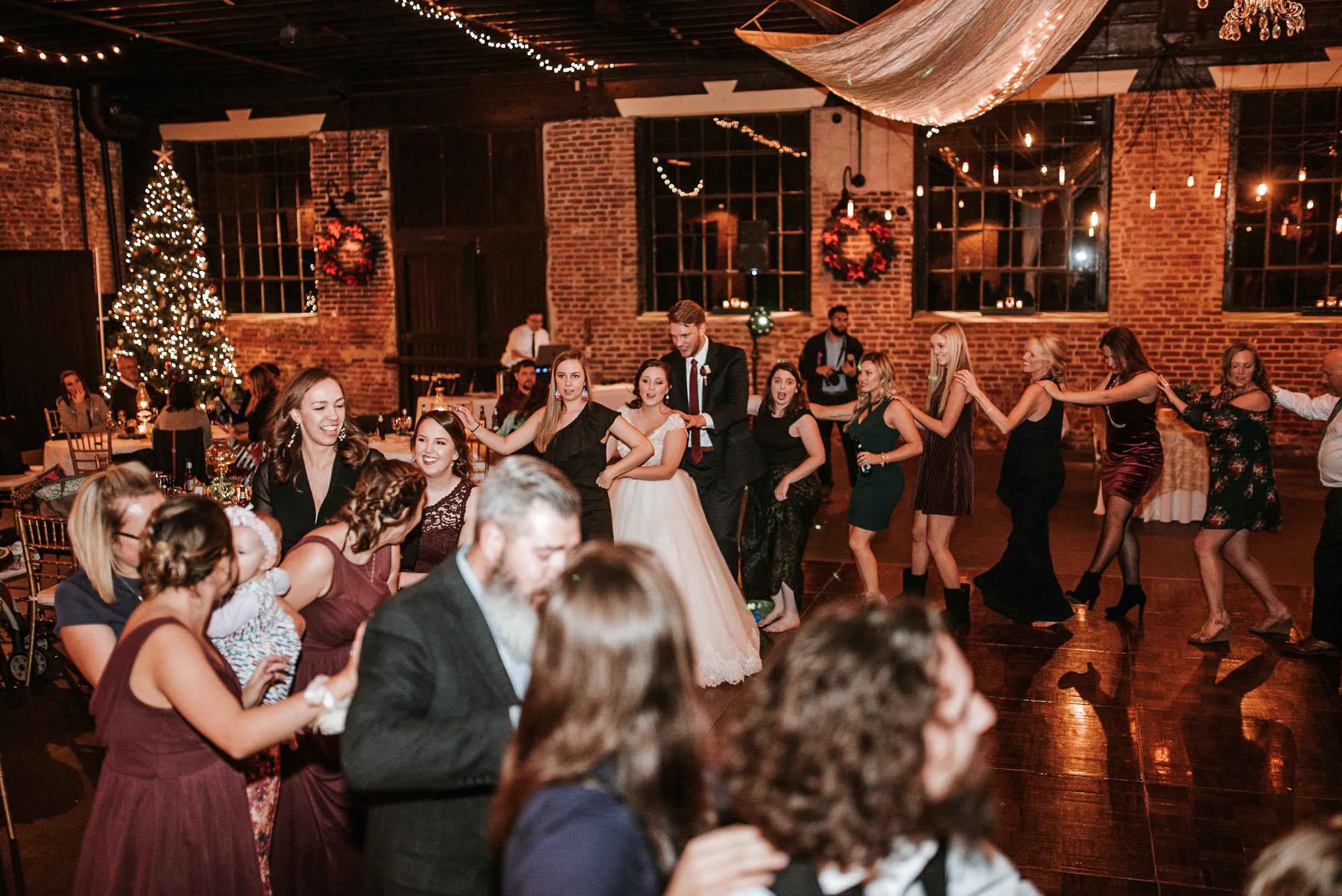 Bride, groom and guests dancing in line
