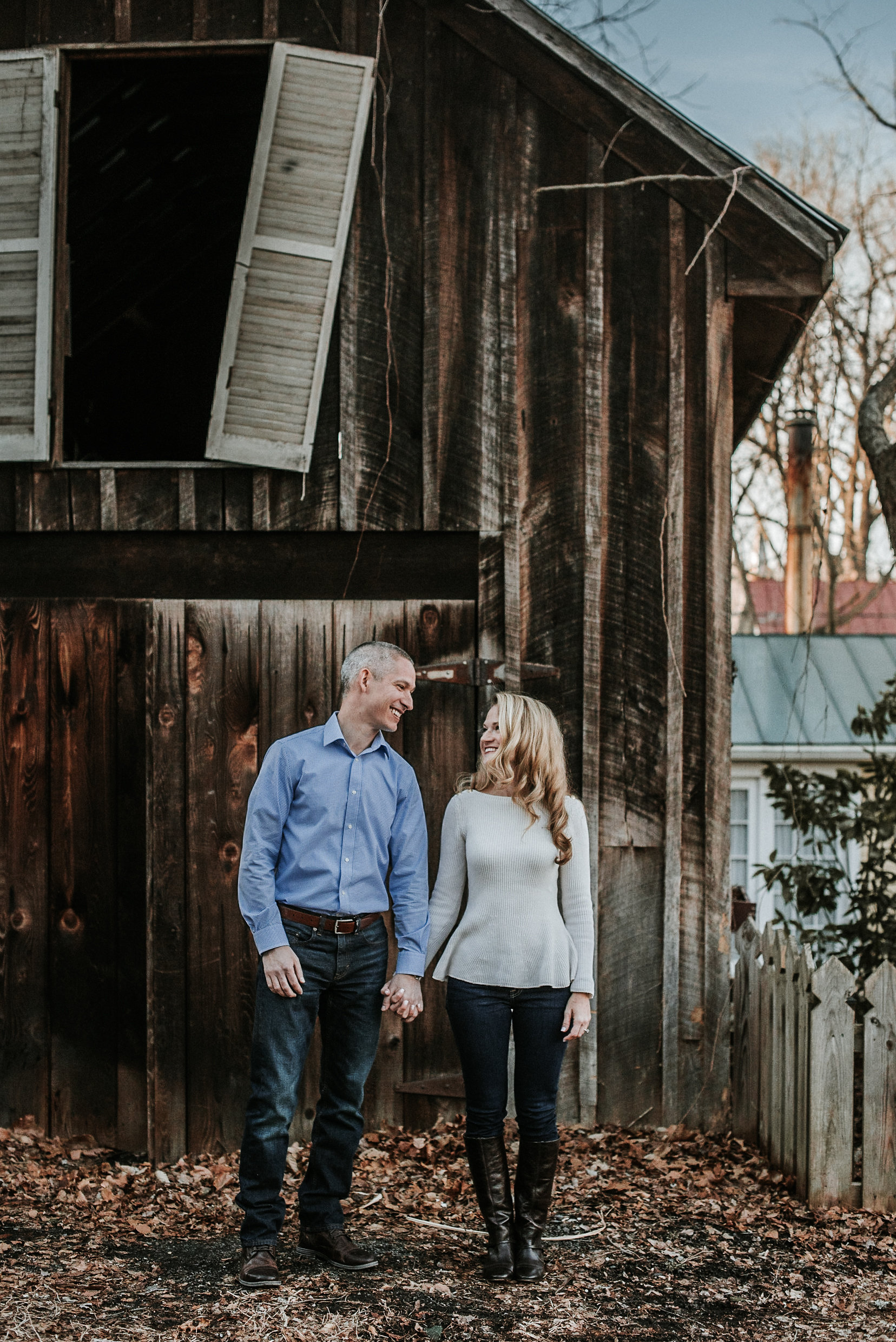 Couple standing in front of old barn