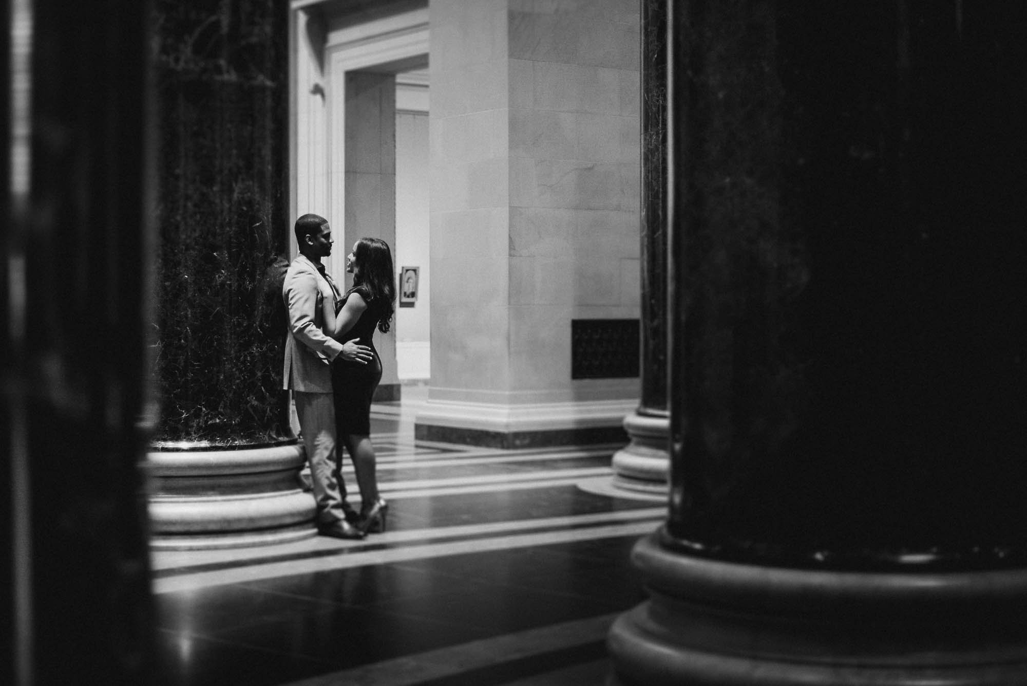 Couple leaning against pillar in black and white
