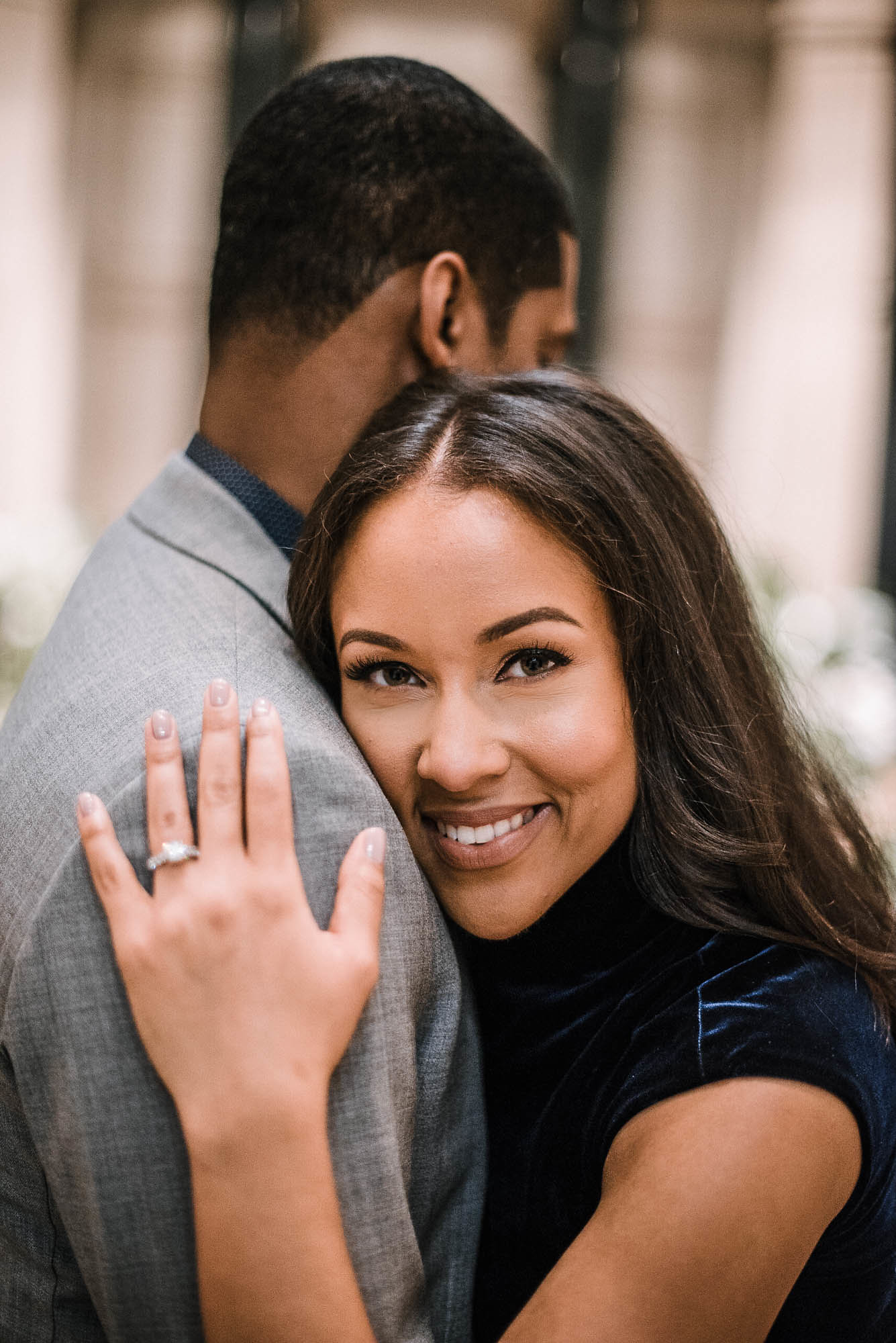 Girl with engagement ring smiling hugging man