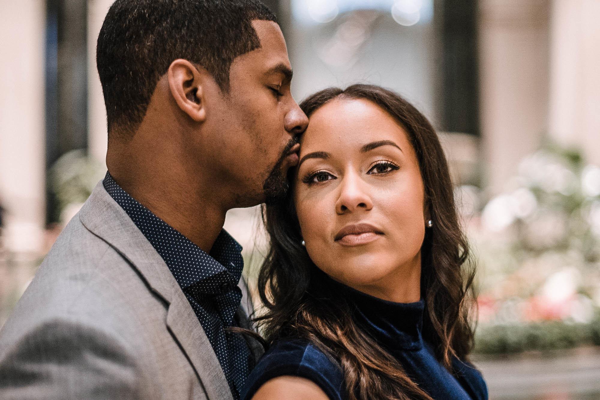 Man kissing fiance's forehead