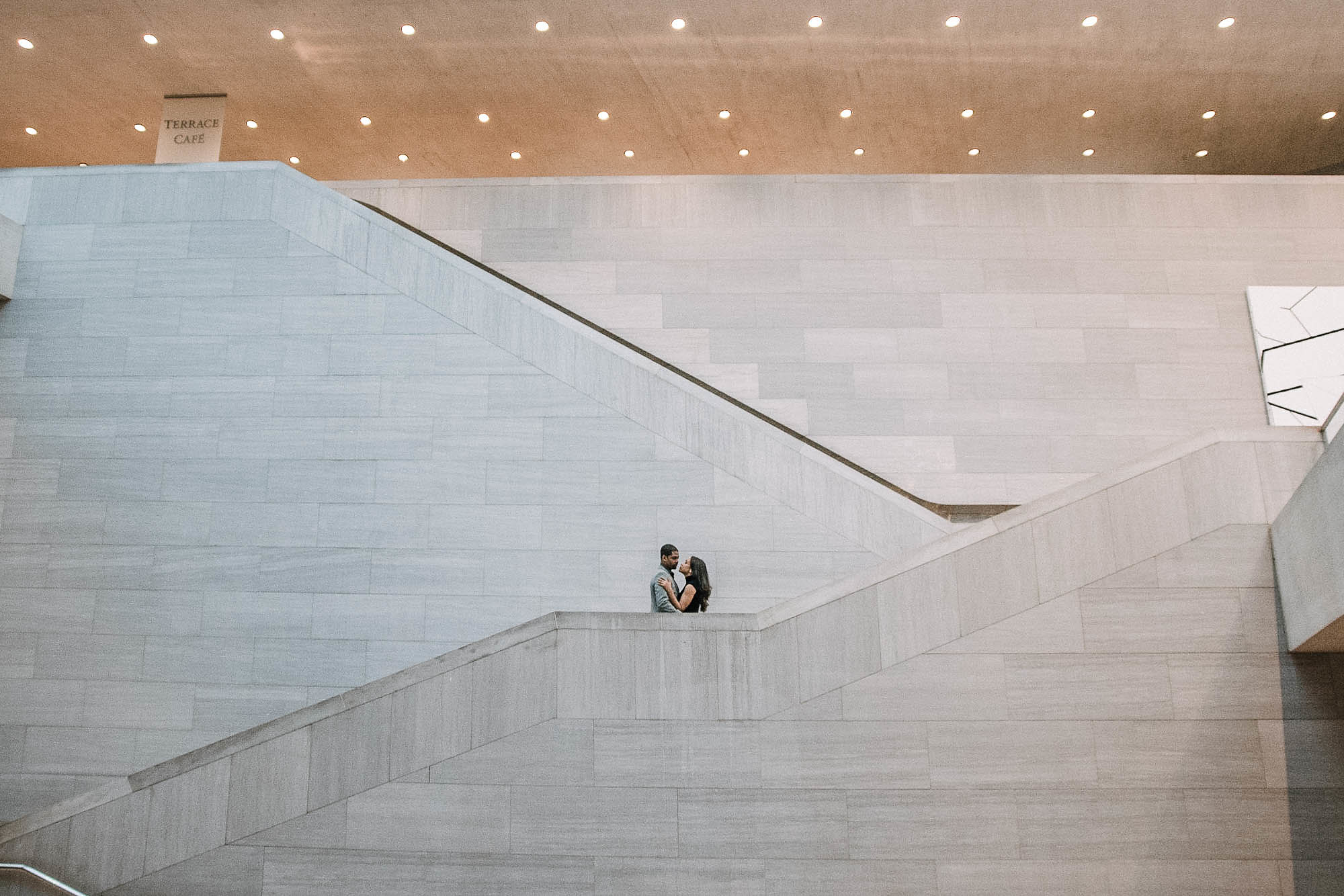 Couple walking down stairs in art gallery