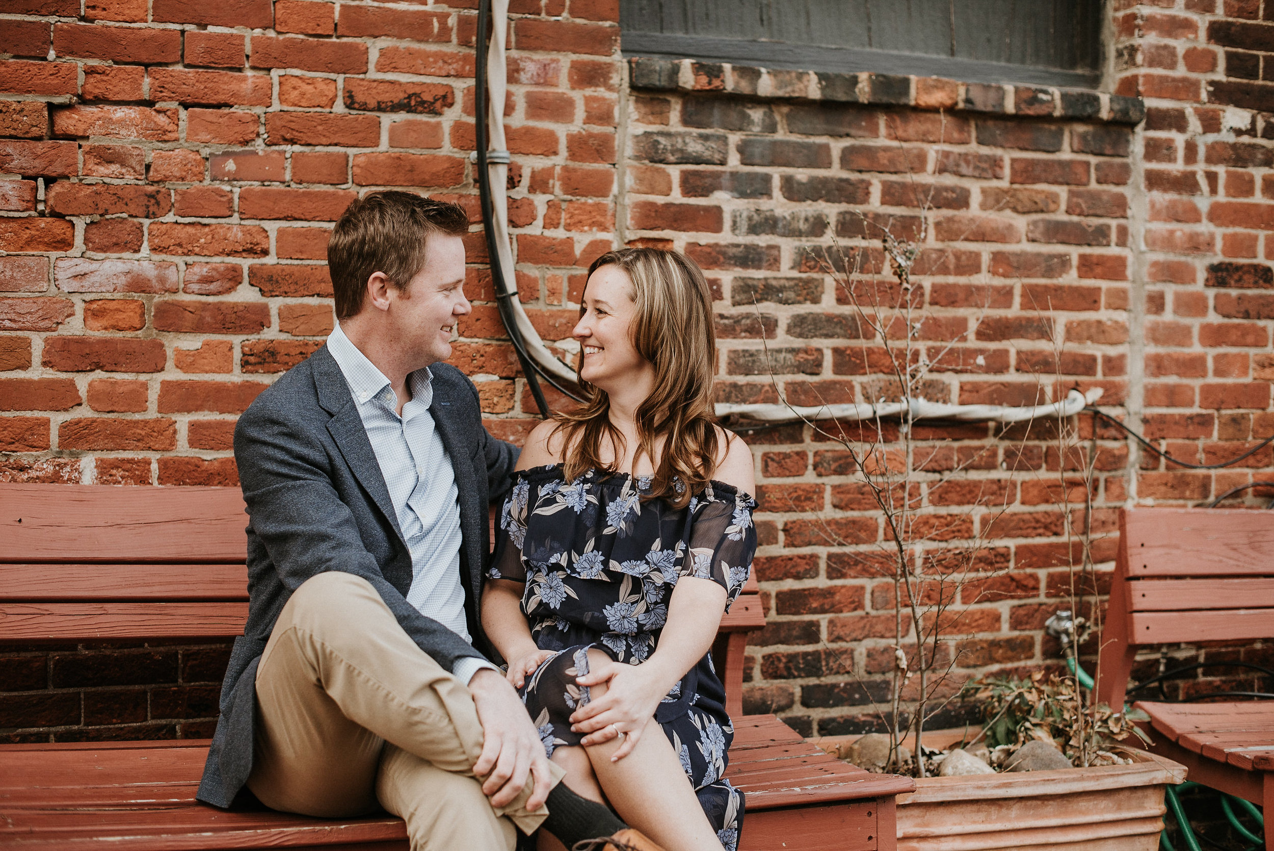 Couple sitting on red bench in front of brick wall