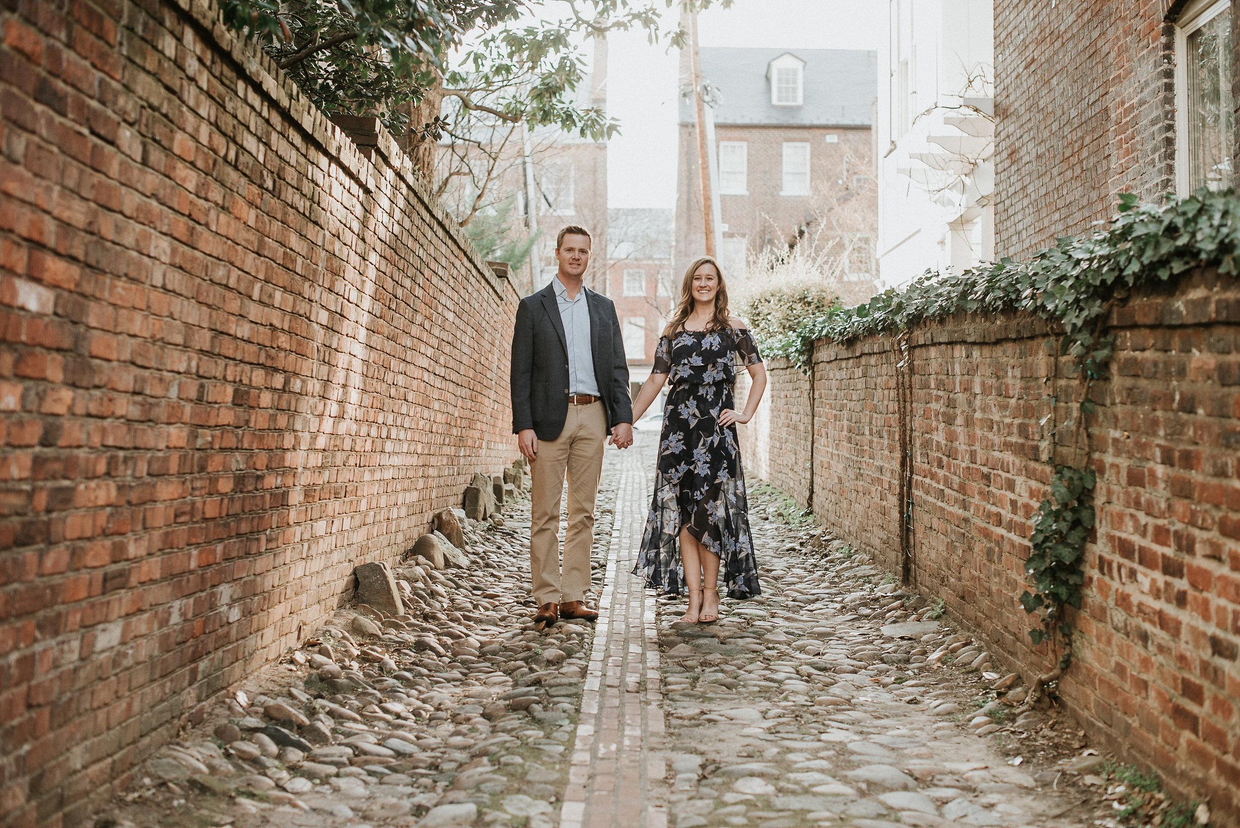 Couple standing in brick alleyway