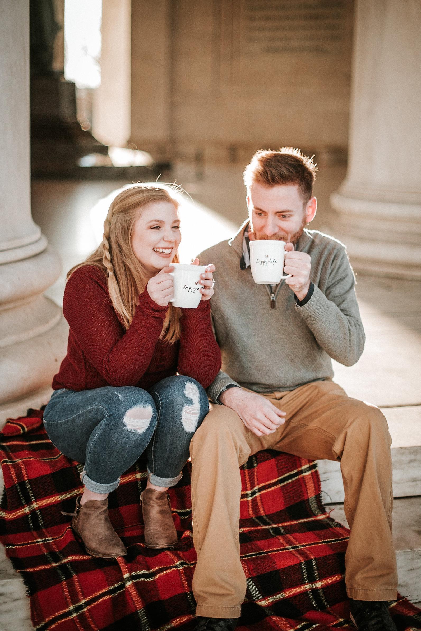 Couple sitting on blanket with mugs