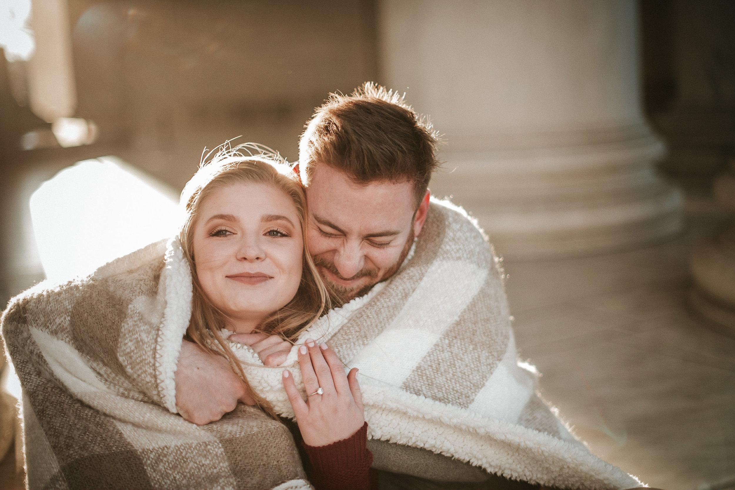 Couple cuddling under blanket