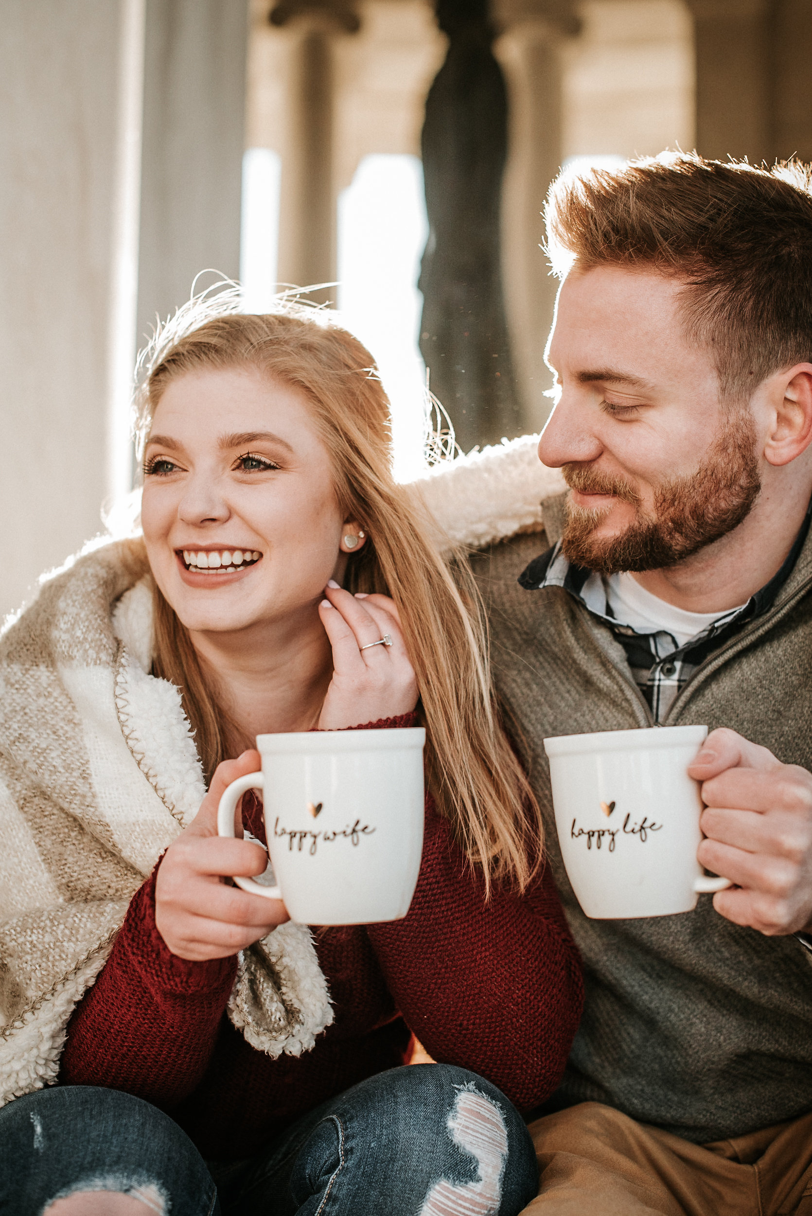 Couple with coffee under blanket