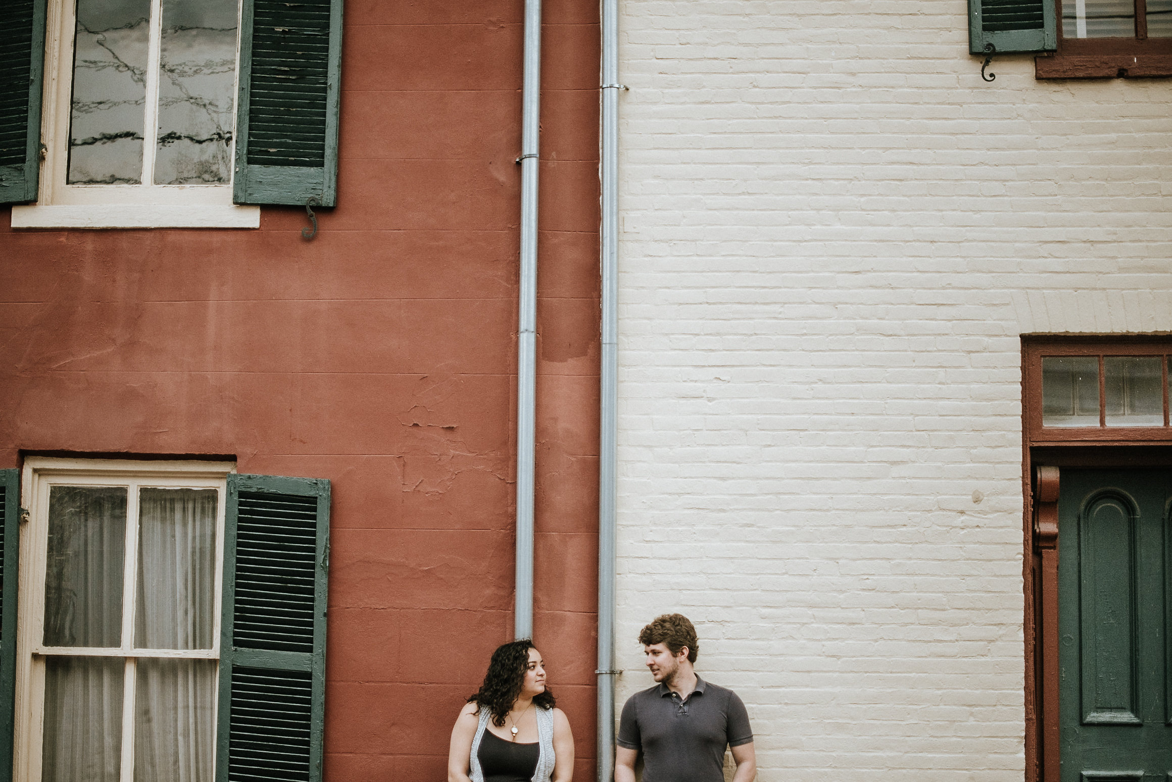 Couple standing against colored brick