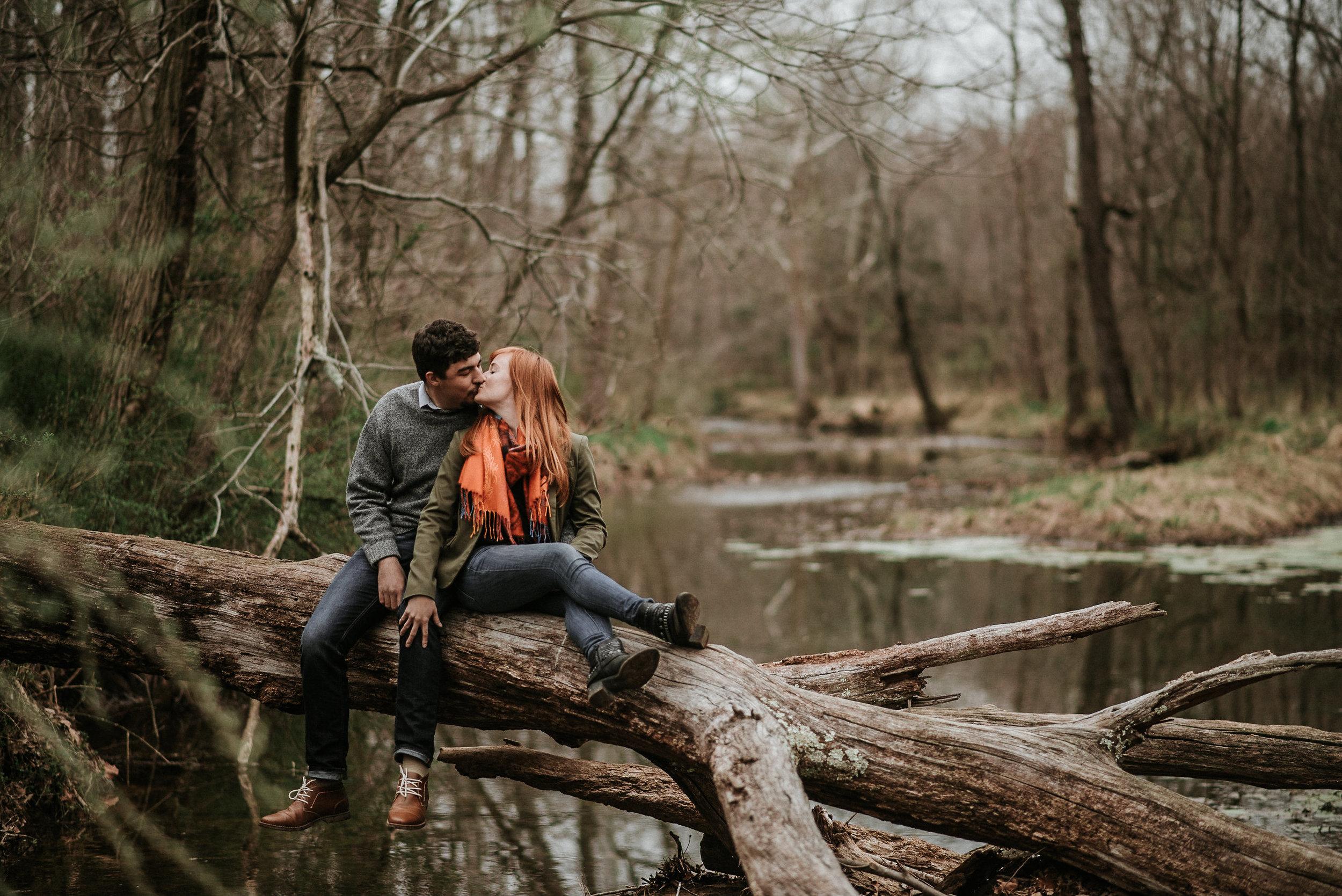 Couple kissing on fallen tree in water