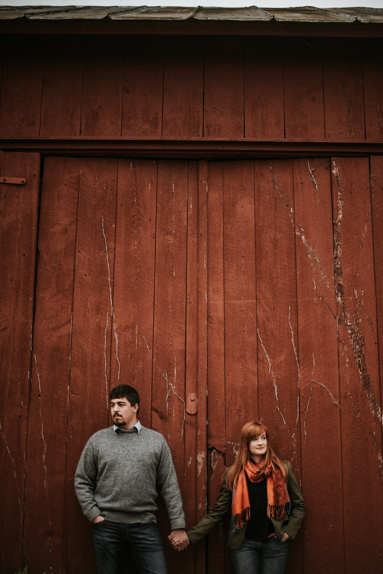 Couple holding hands against barn