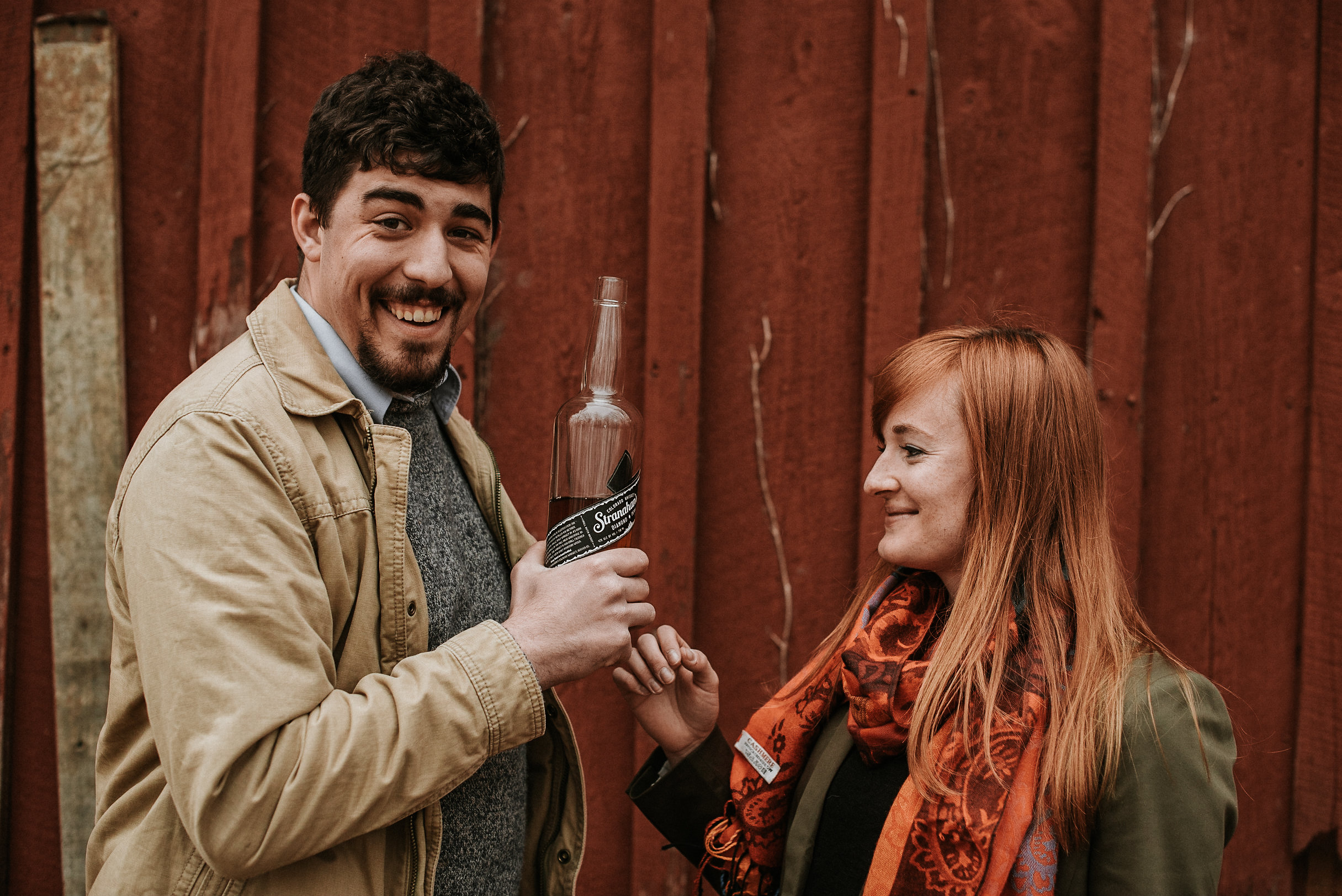 Laughing woman and man holding whiskey bottle