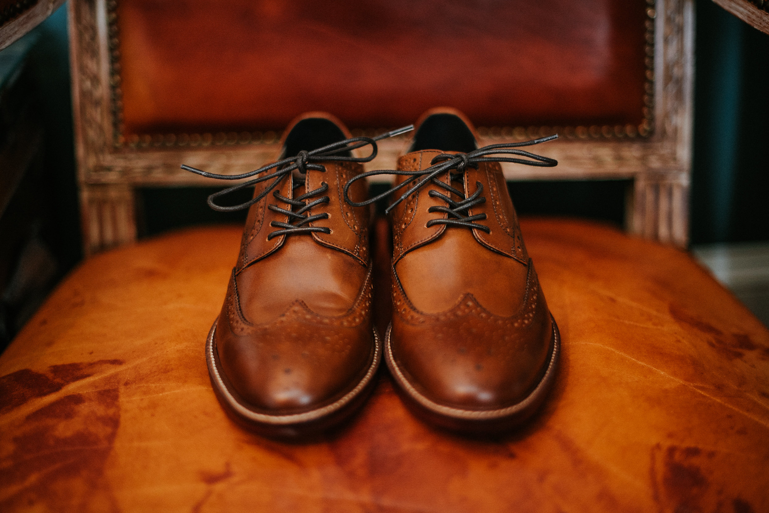 Groom's shoes sitting on leather chair
