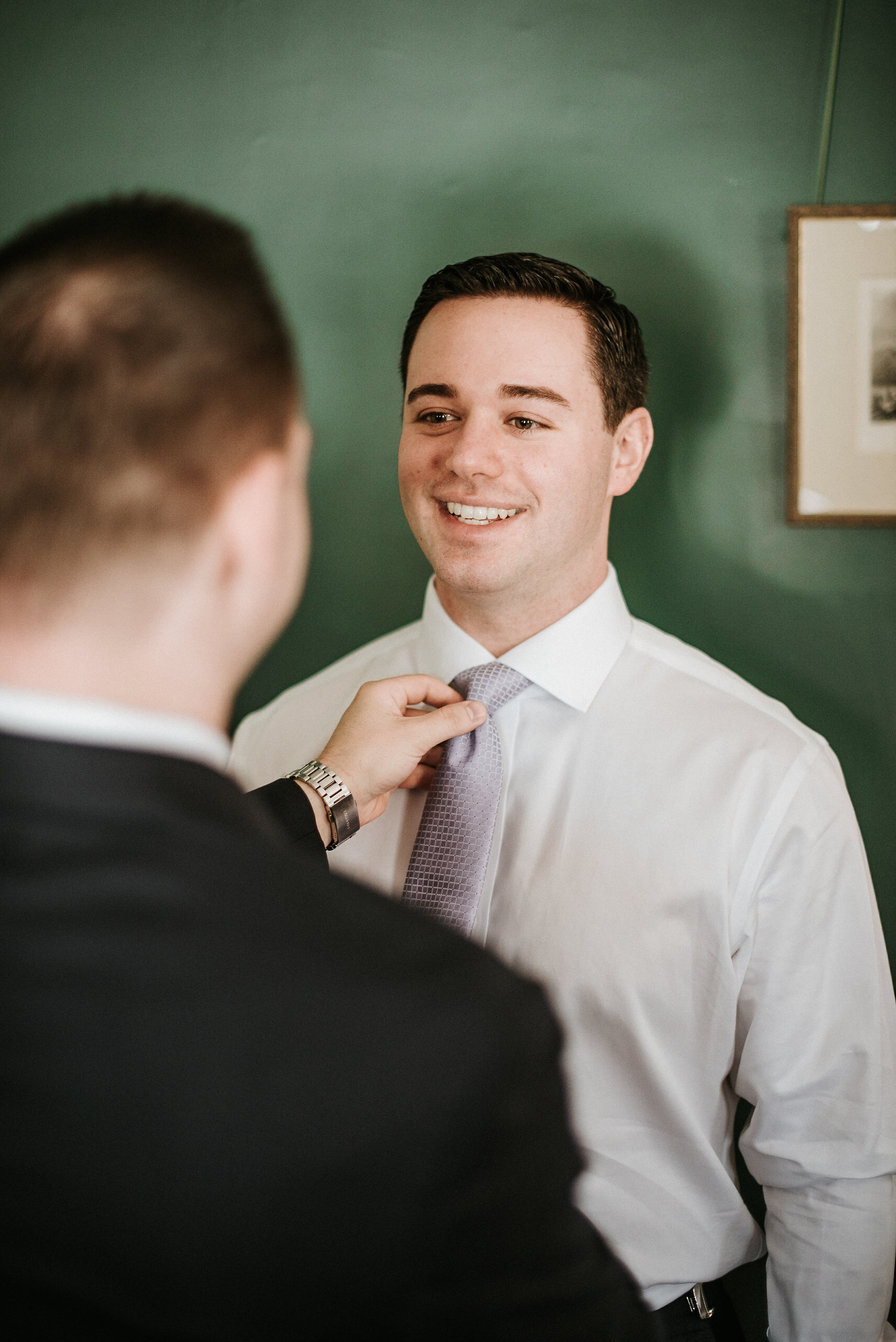 Groomsman helping groom with tie