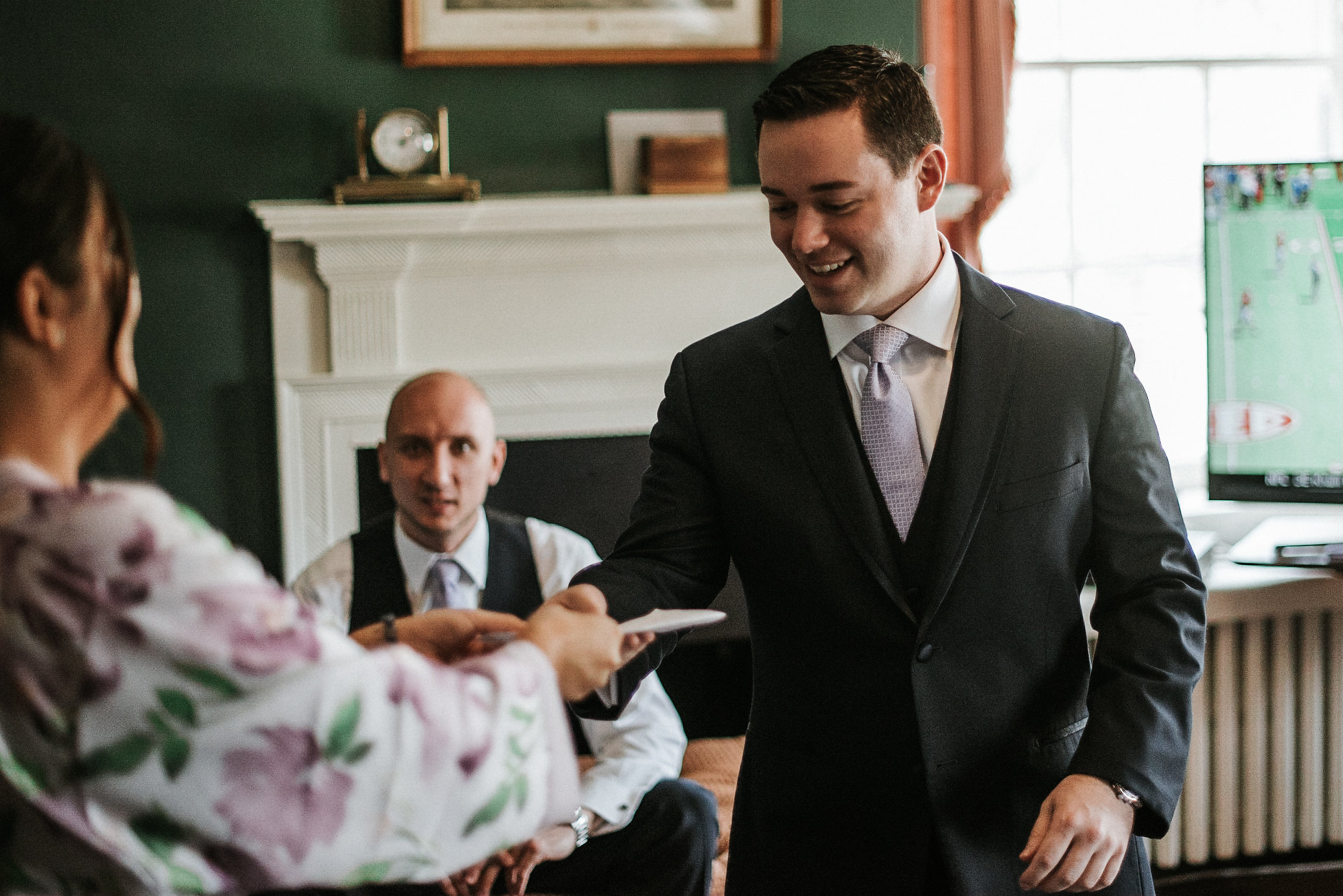 Bridesmaid delivering letter to groom