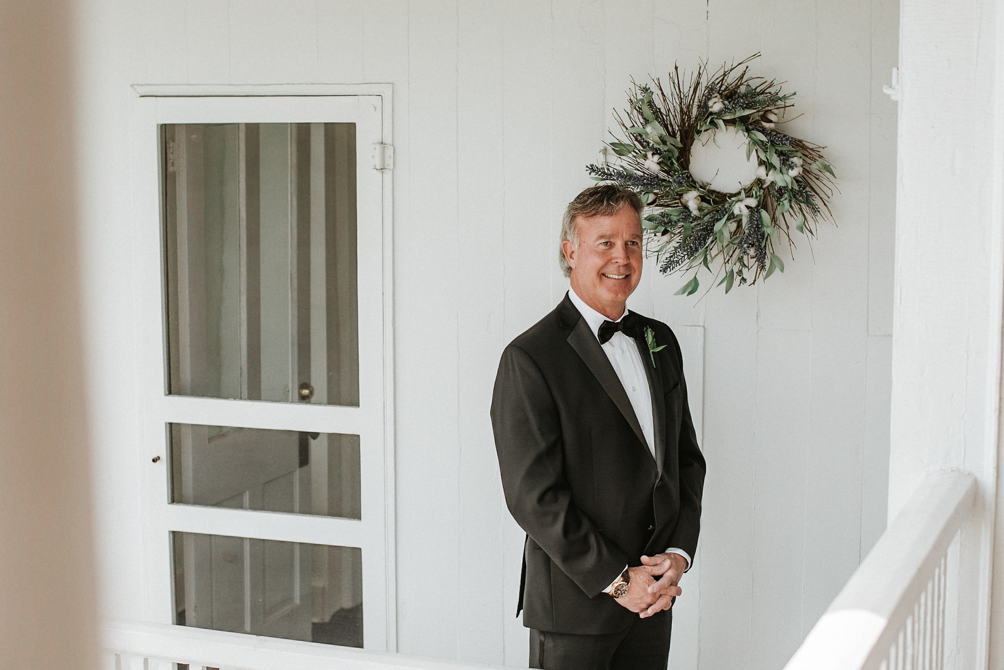 Father of the bride standing on balcony