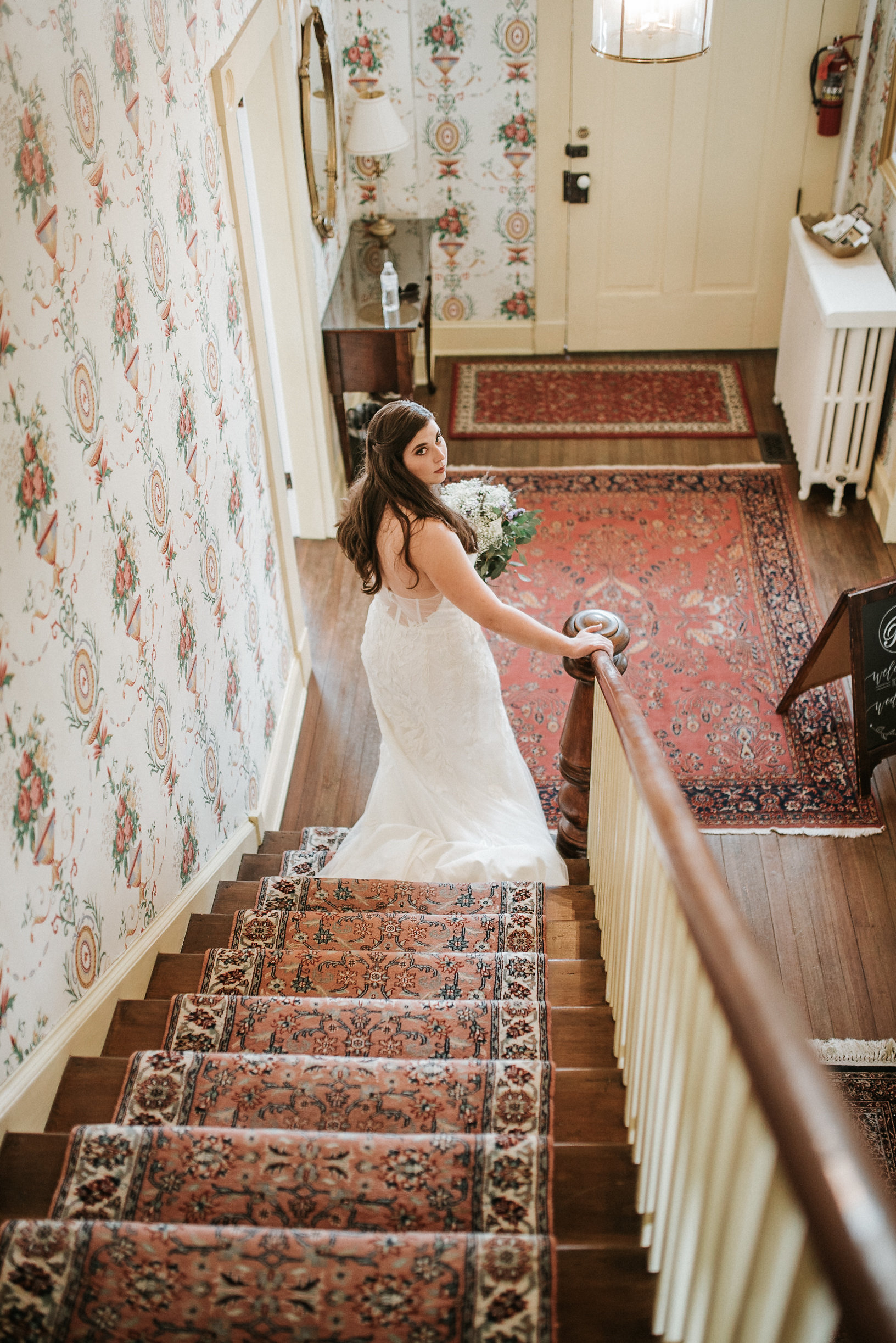 Bride looking over shoulder up stairs
