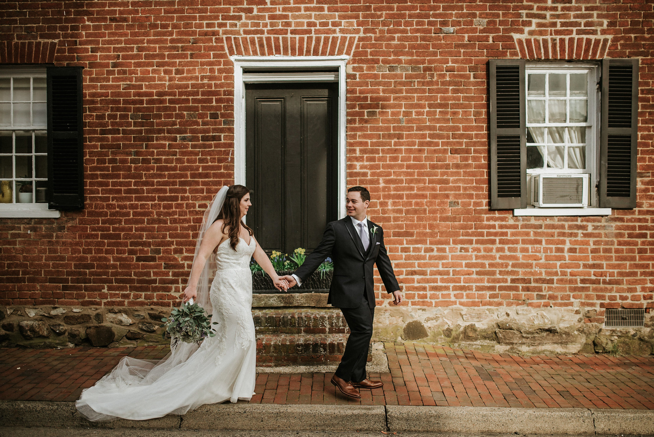 Bride and groom walking on stone sidewalk