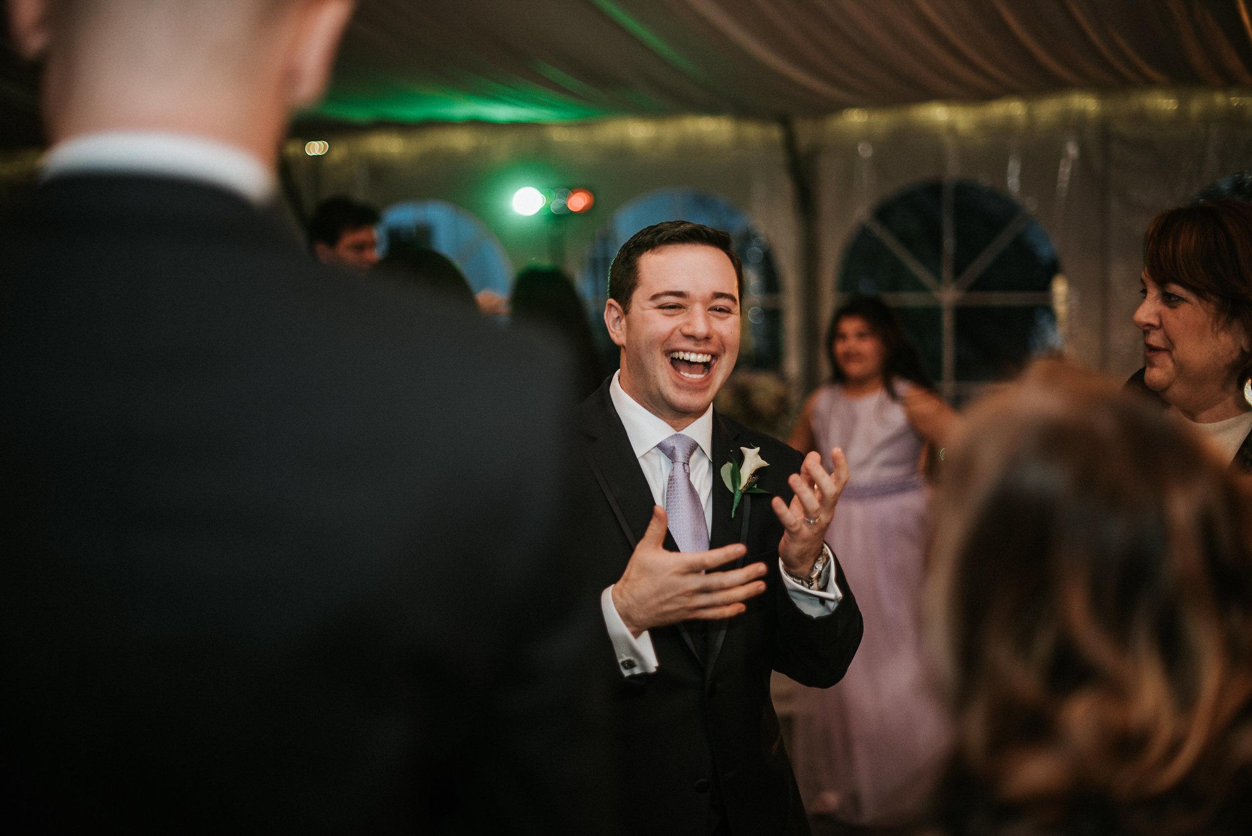 Groom laughing at wedding