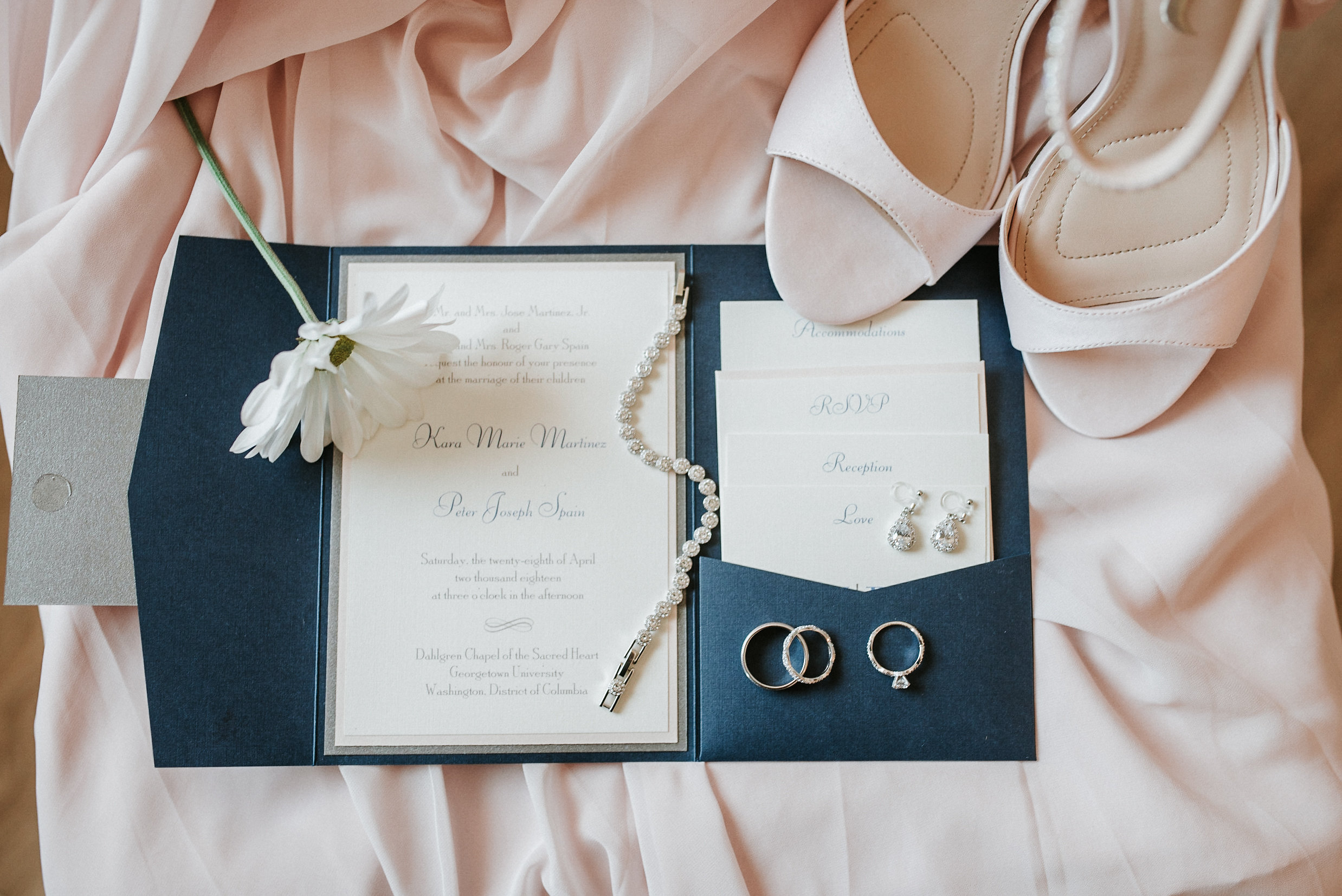 Bridal shoes and jewelry on top of invitation