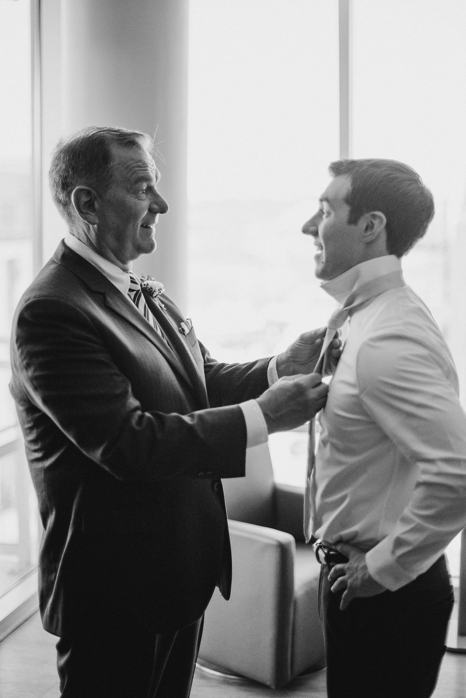 Groom's father helping him with tie