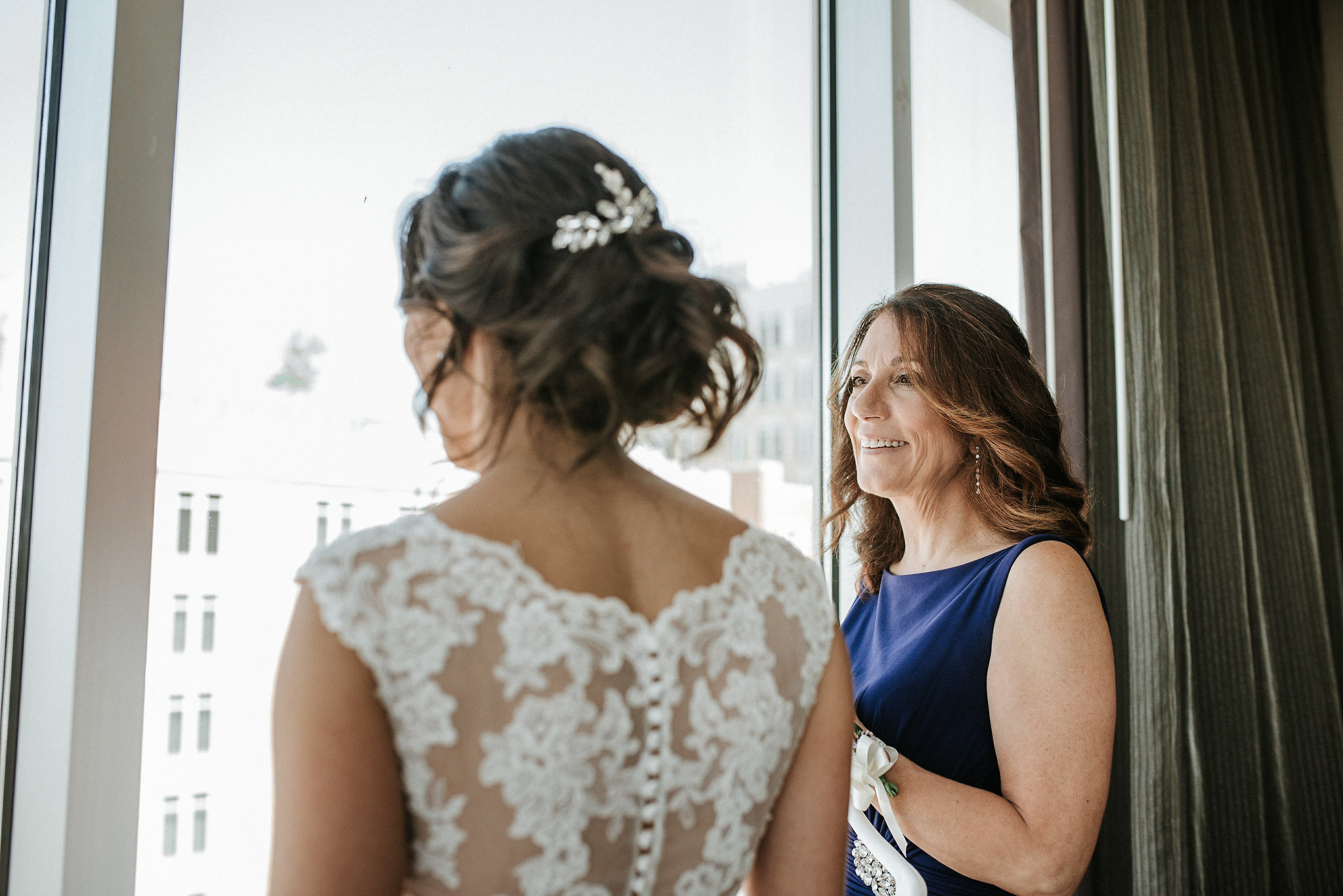 Bride and mother looking out window