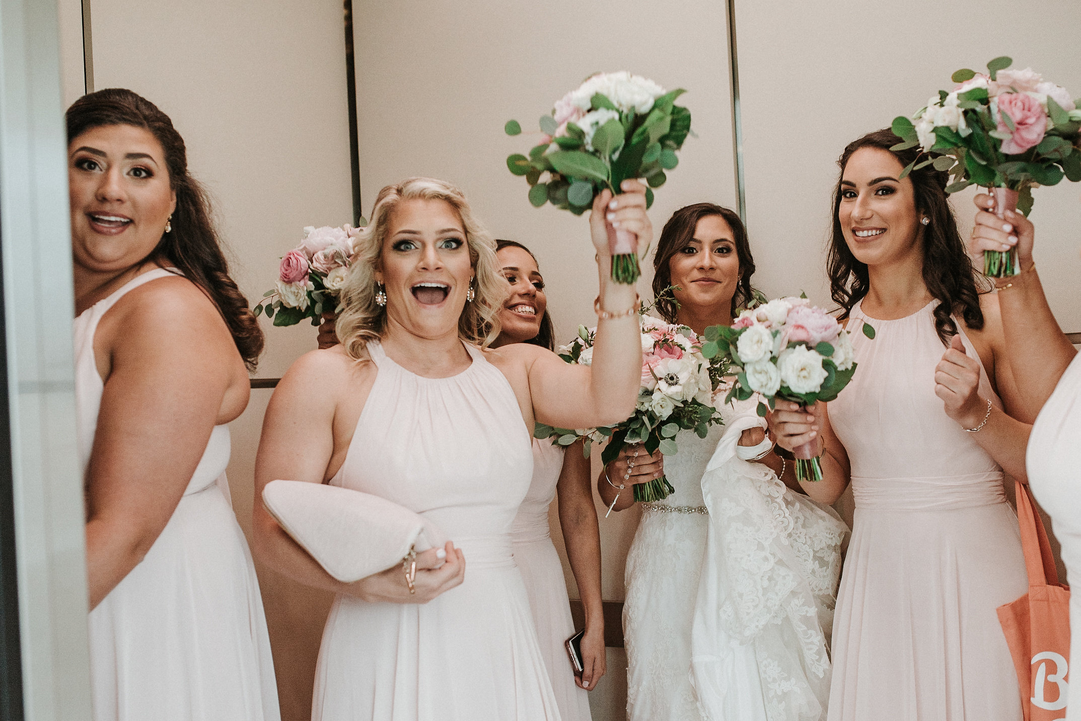 Bride on elevator with bridesmaids