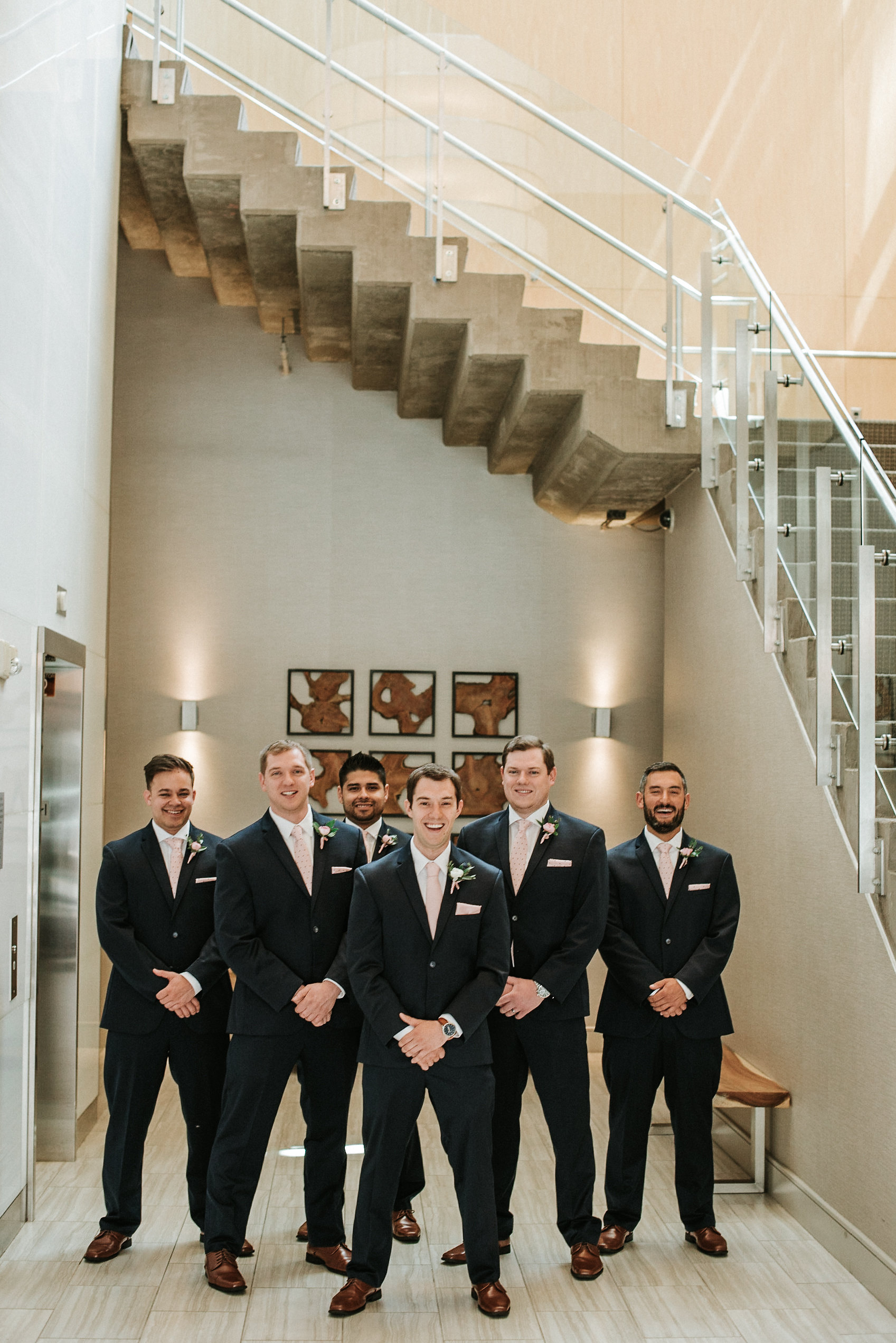 Groom and groomsmen under stairs
