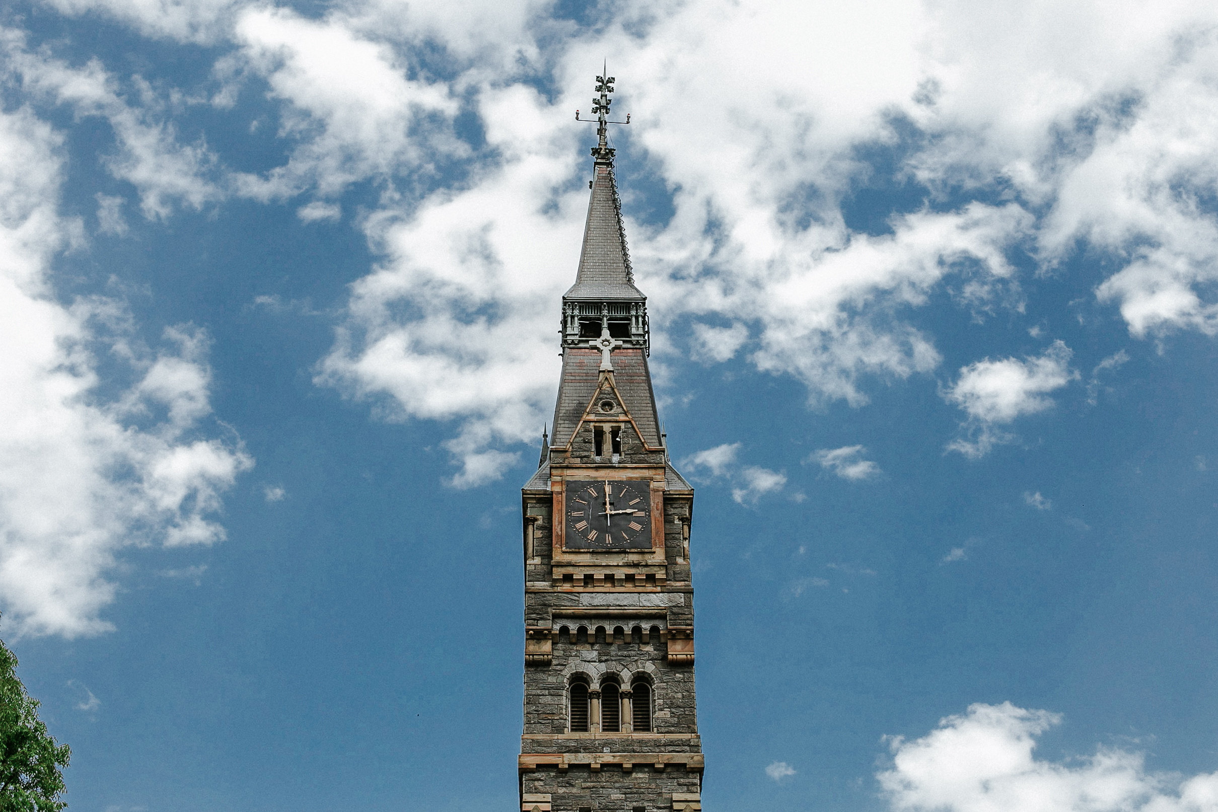 Church steeple against cloudy blue sky
