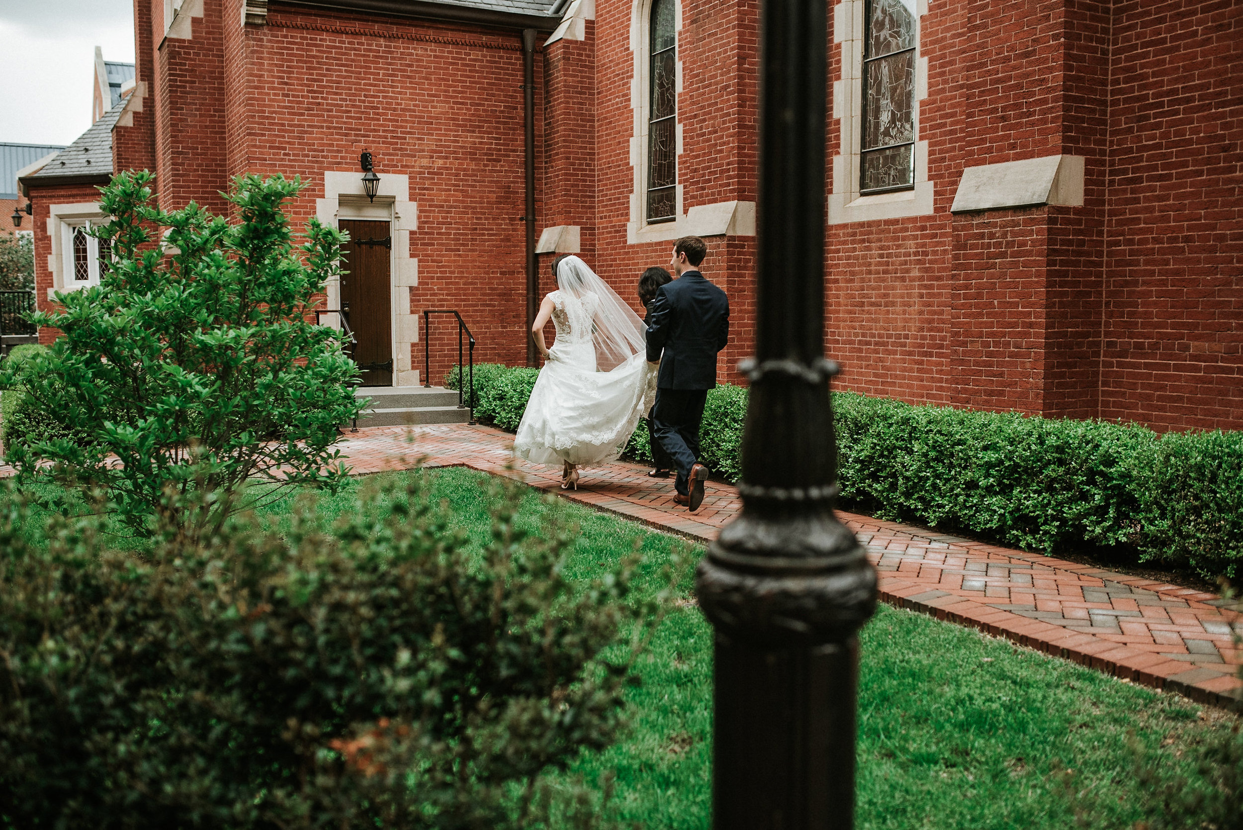 Bride and groom running behind church
