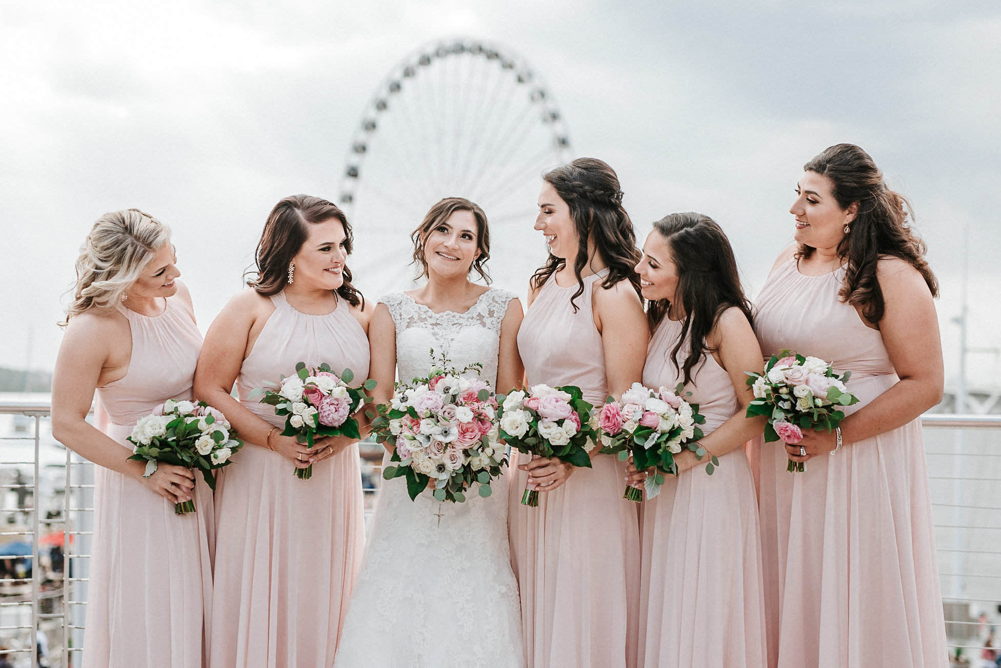 Bride and bridesmaids standing in front of ferris wheel