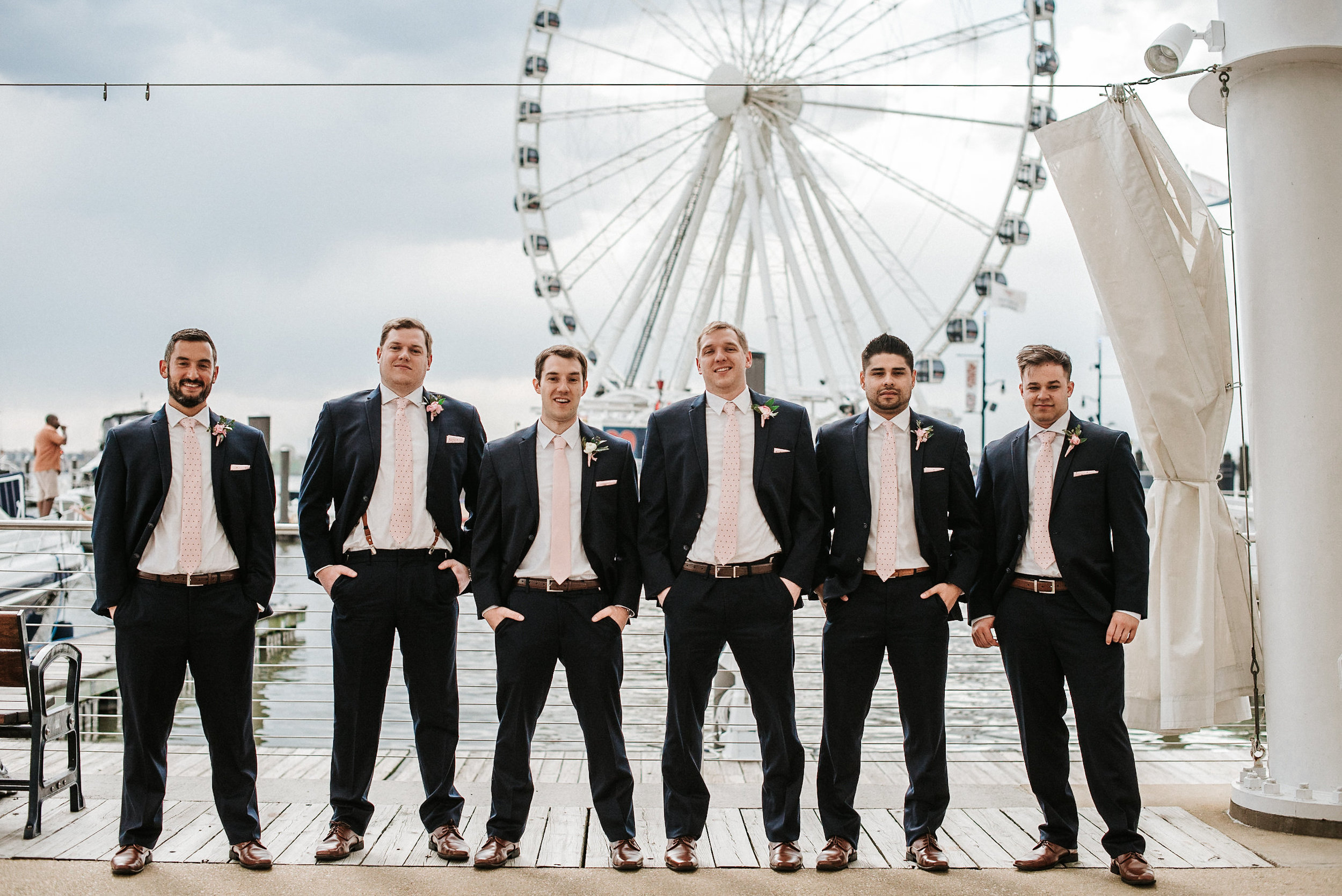 Groom and groomsmen in front of ferris wheel