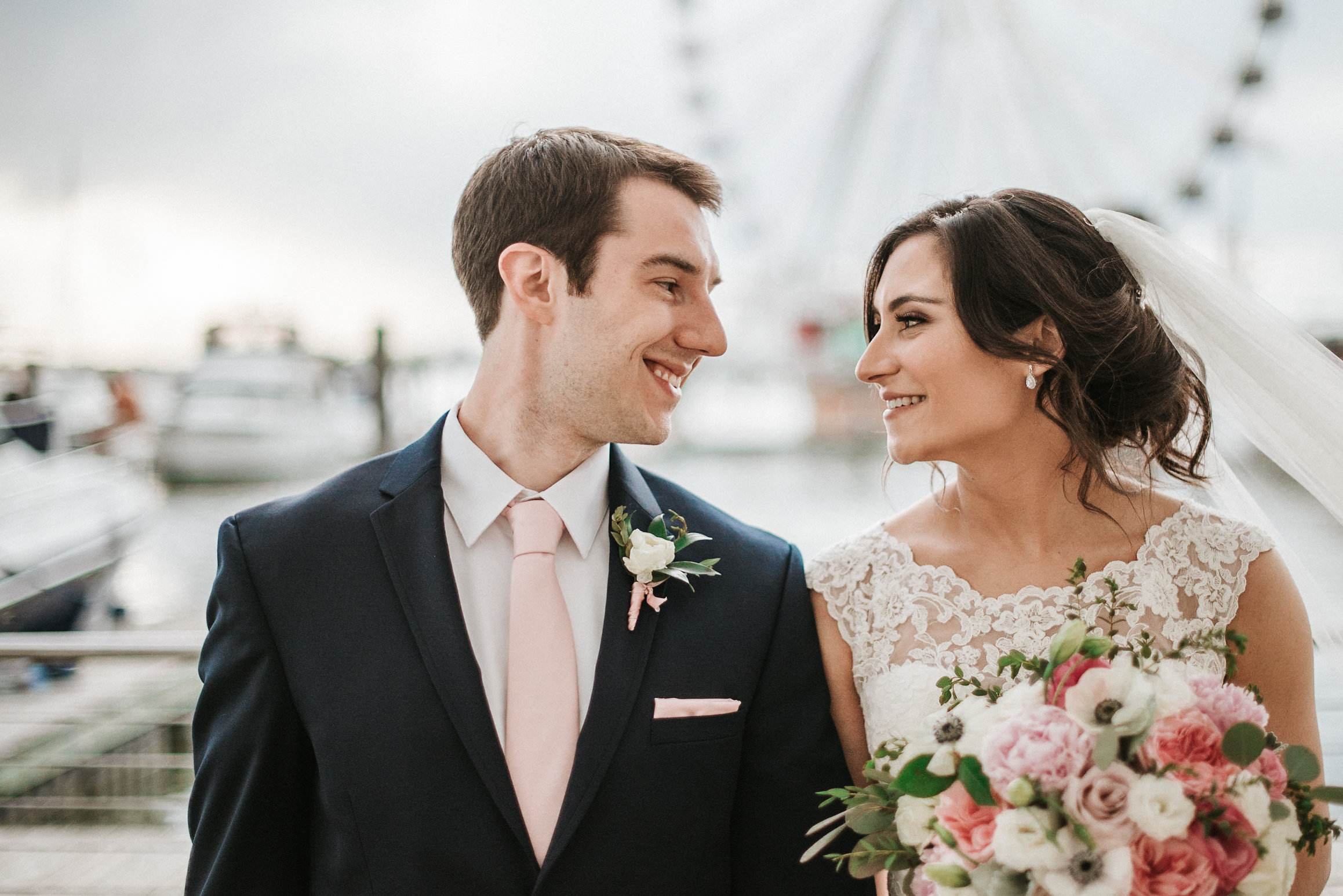Bride and groom smiling at one another in front of ferris wheel