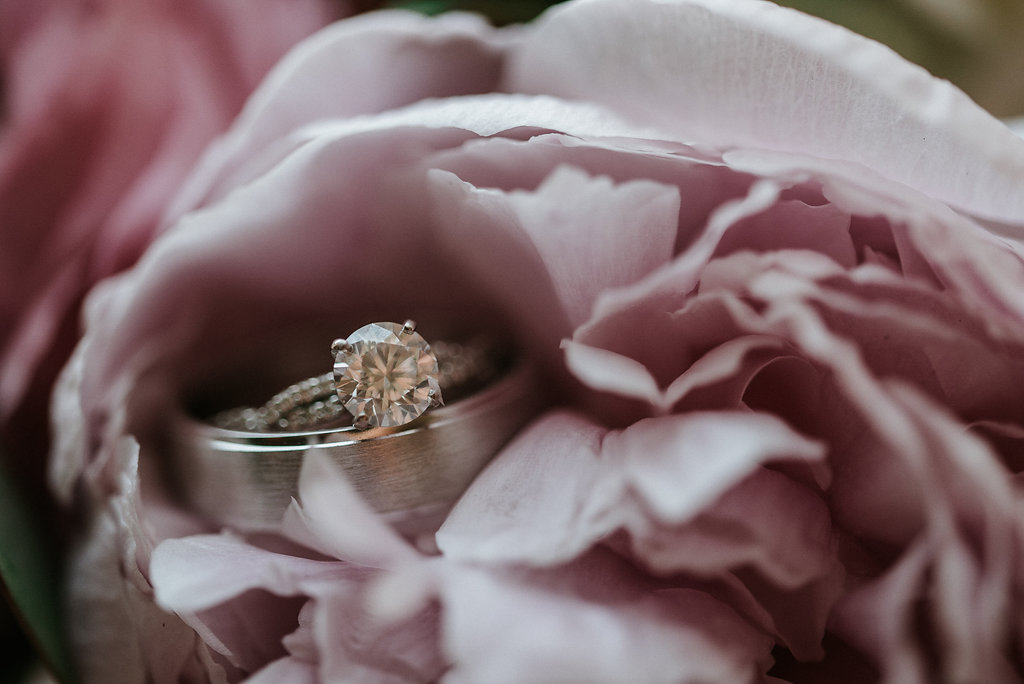 wedding rings sitting in floral