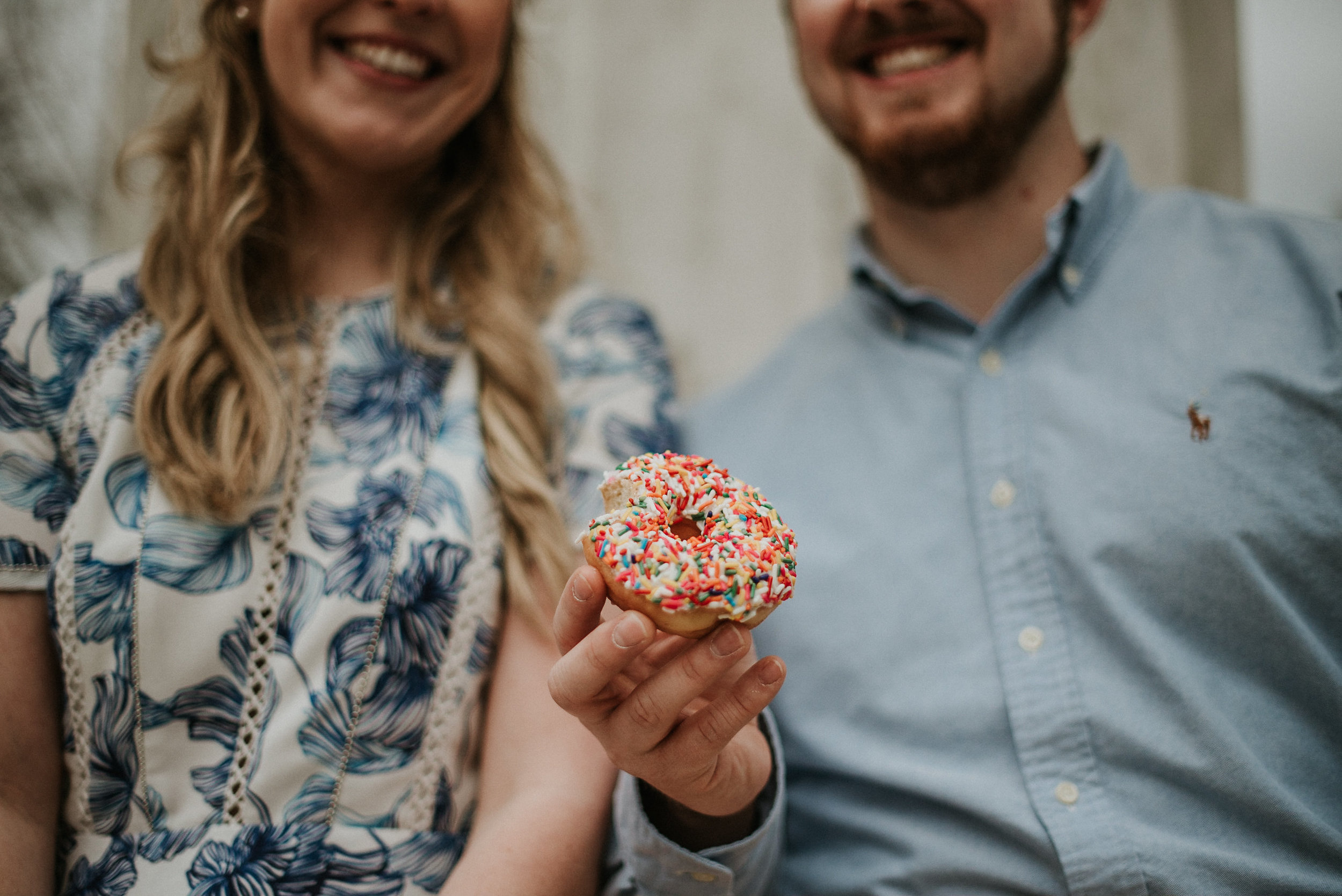 Couple holding sprinkle donut