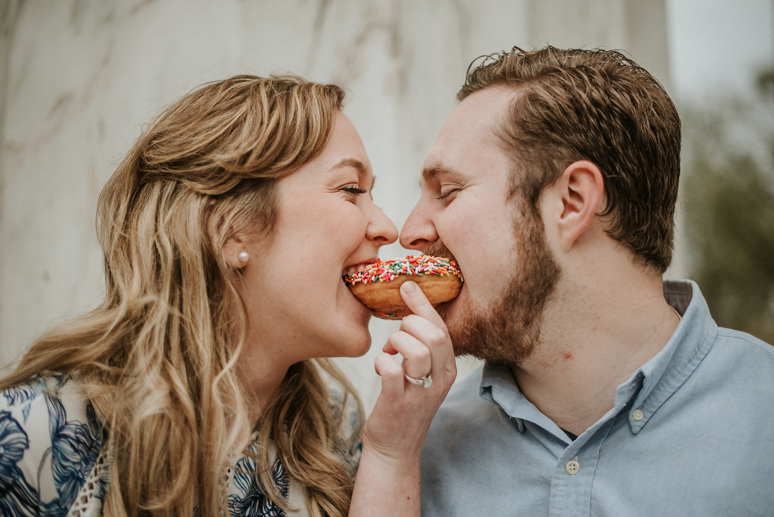 Couple taking a bite from donut