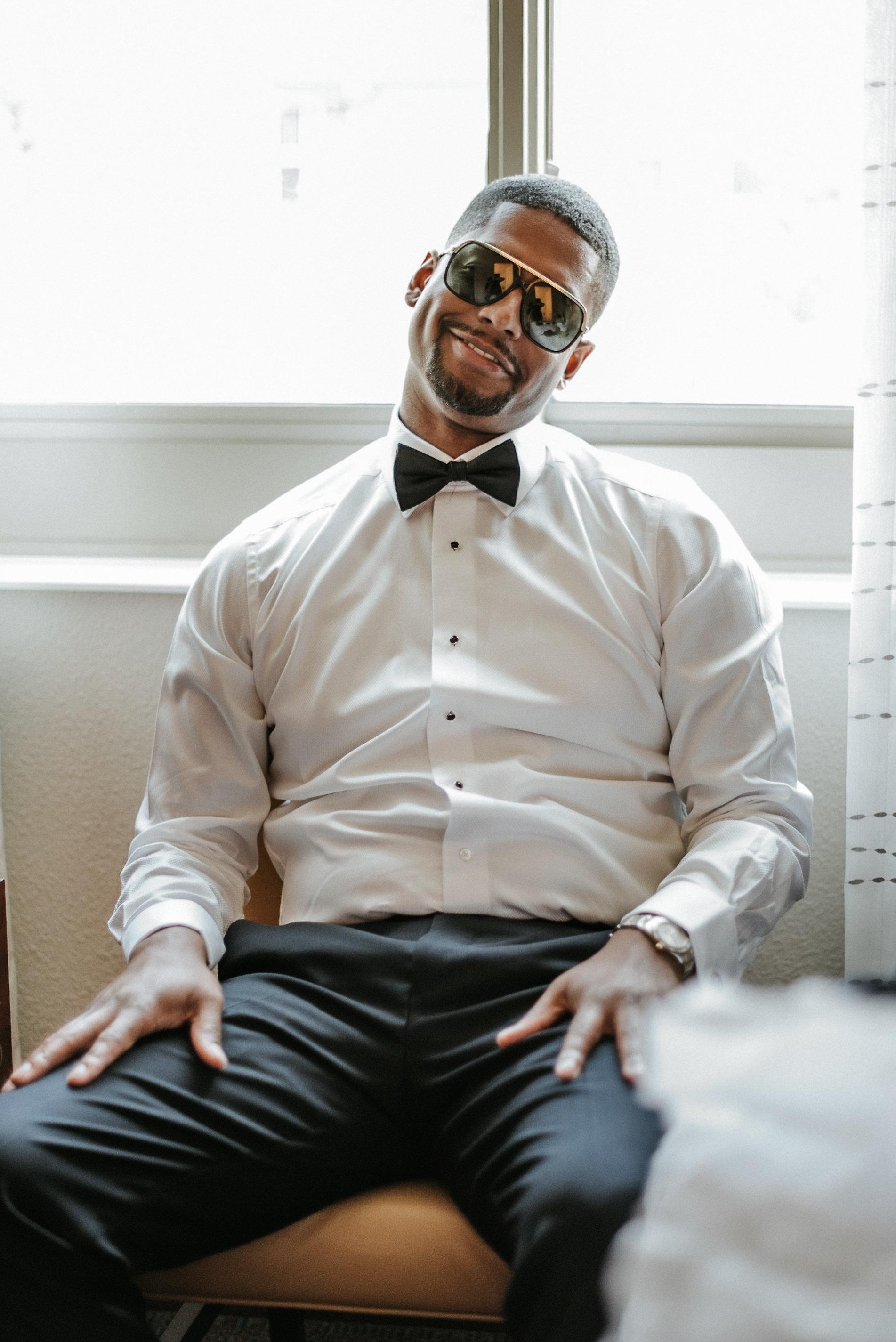Groom modeling sunglasses before wedding