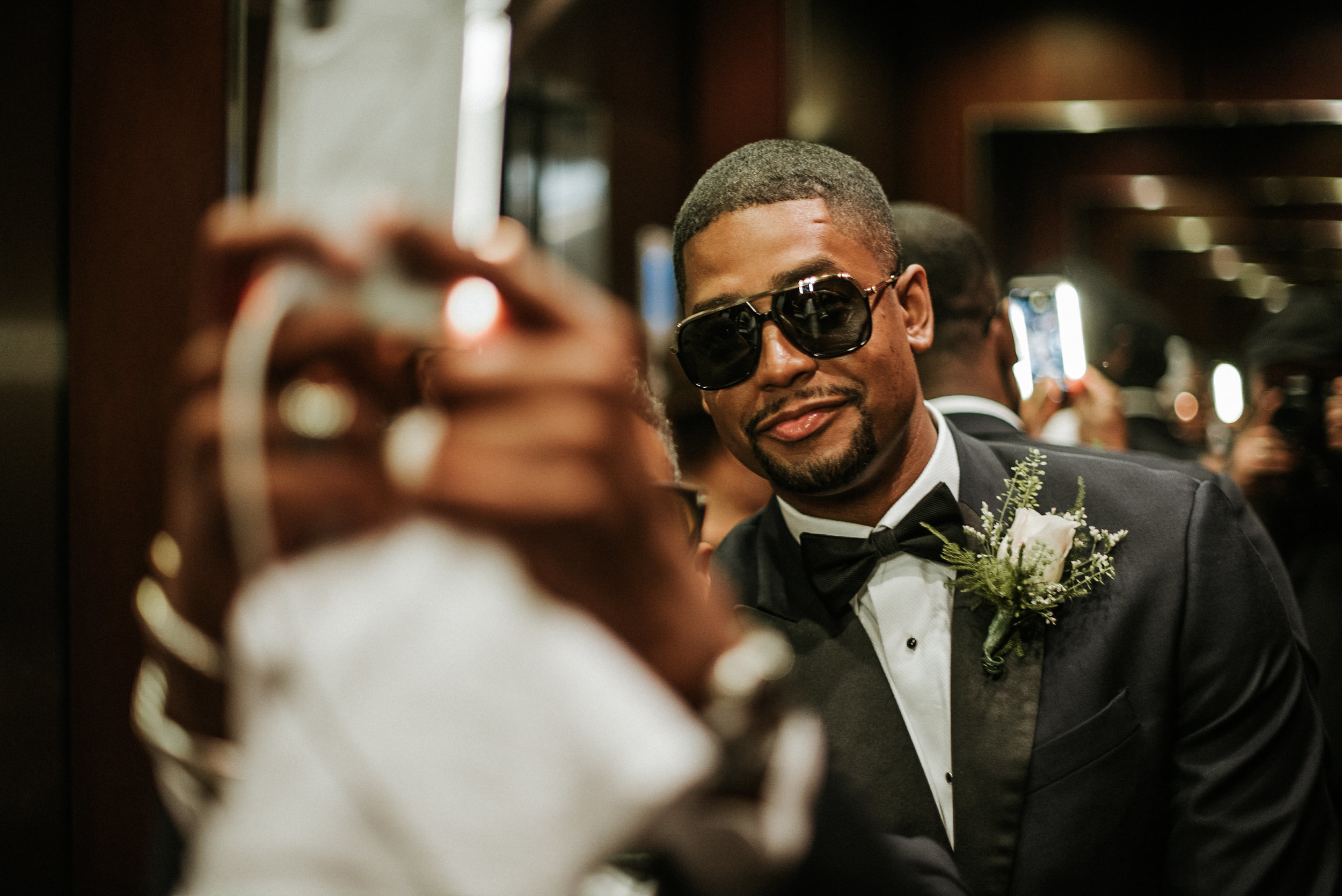 Groom taking selfie before wedding