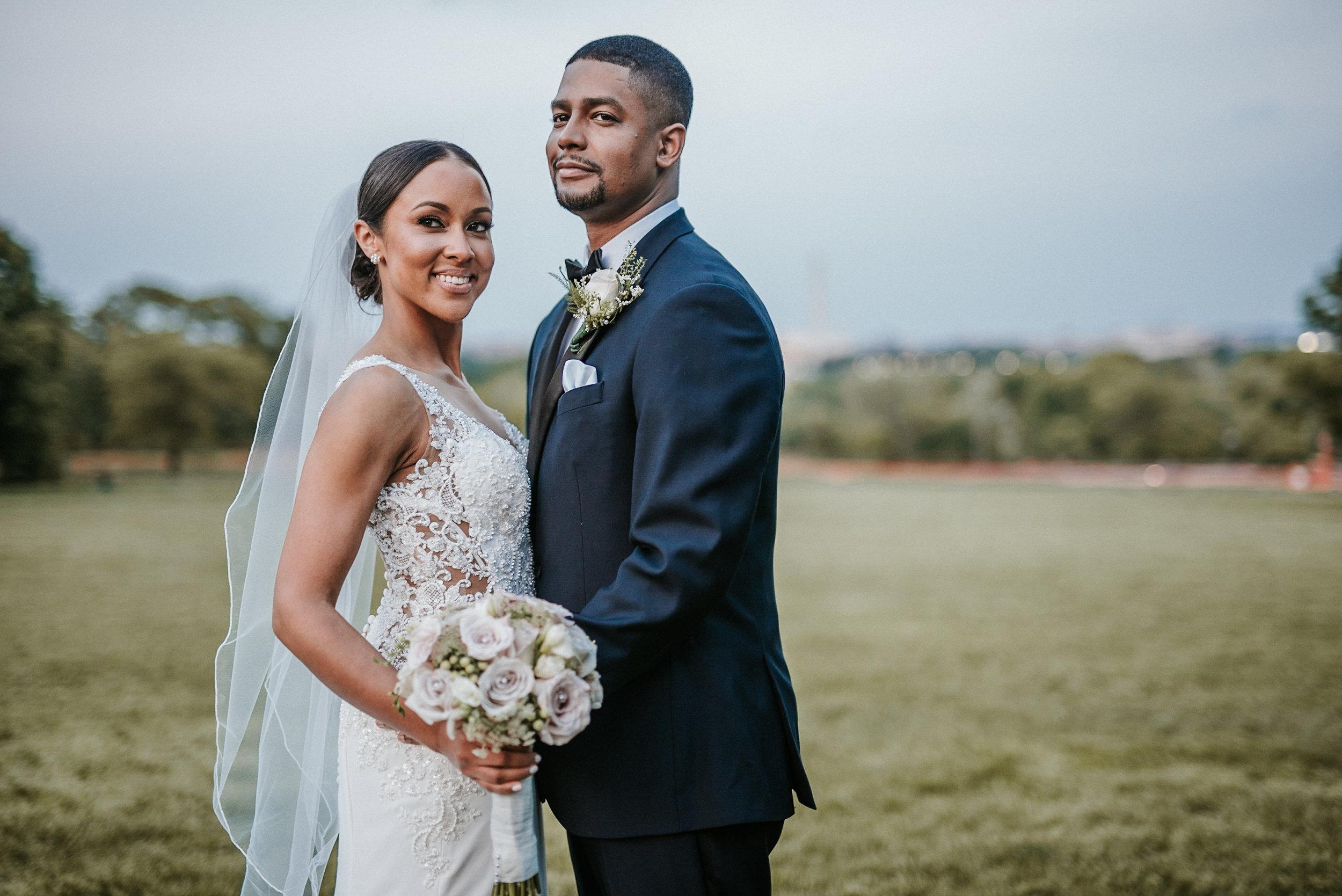 Bride and groom posing in field