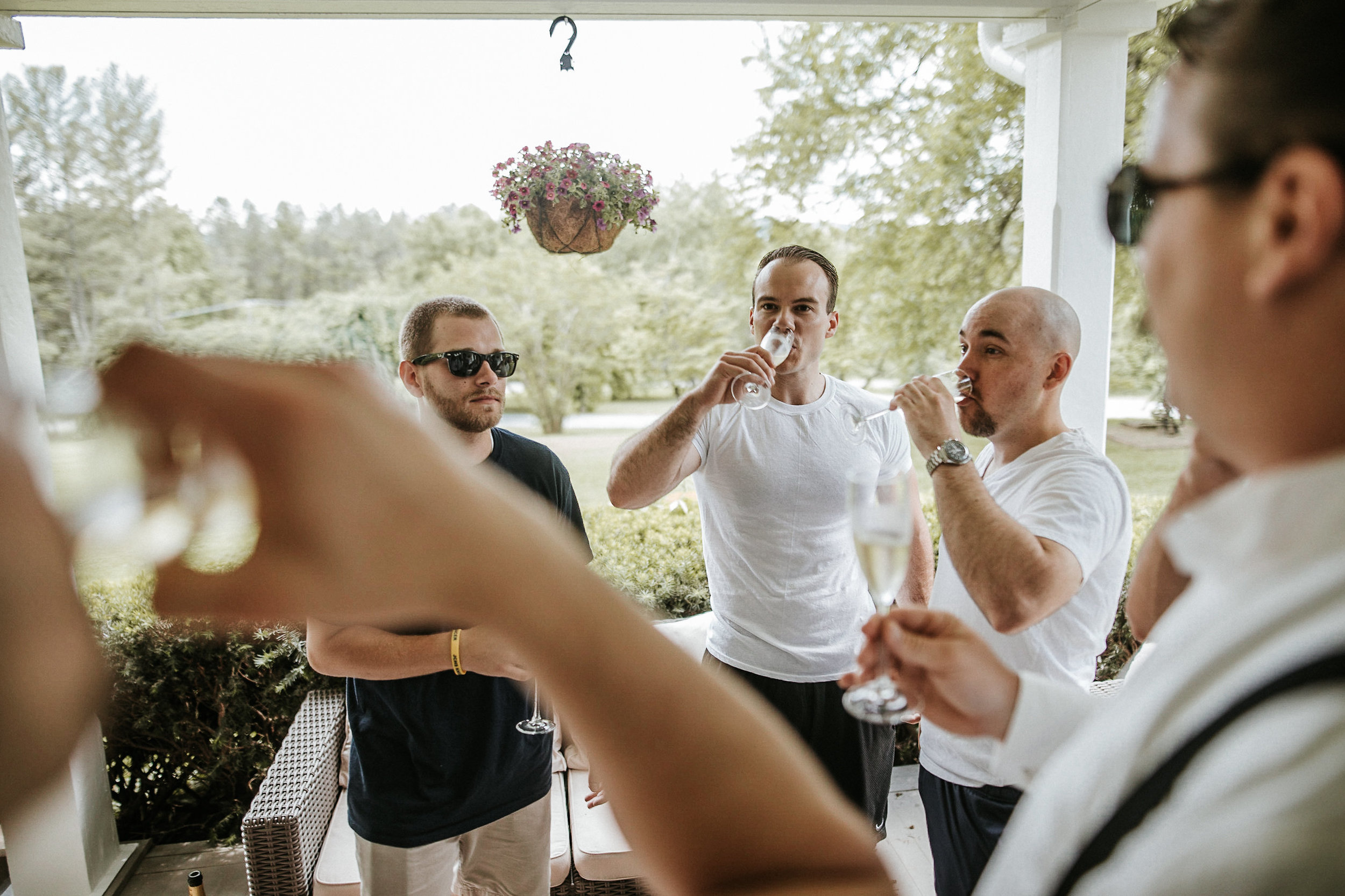 Groom drinking champagne with groomsmen