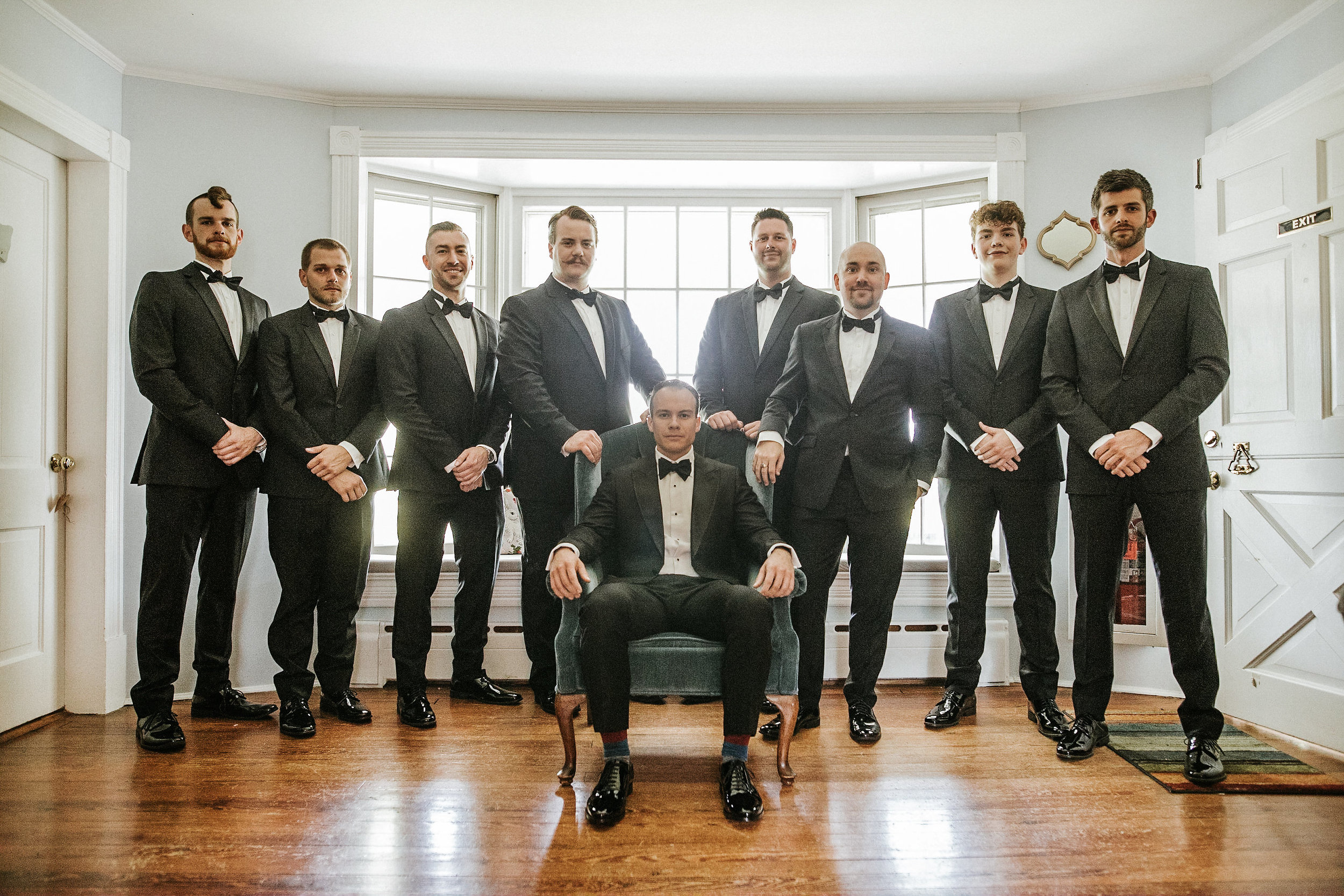 Groom sitting in chair surrounded by groomsmen
