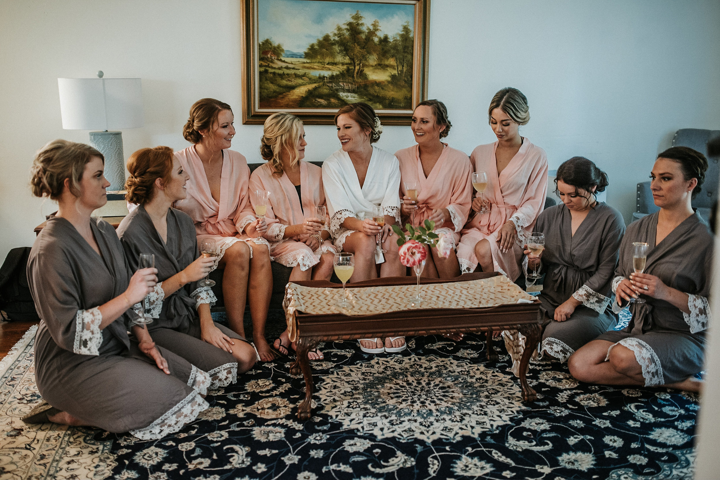 Bride sitting on sofa with bridesmaids