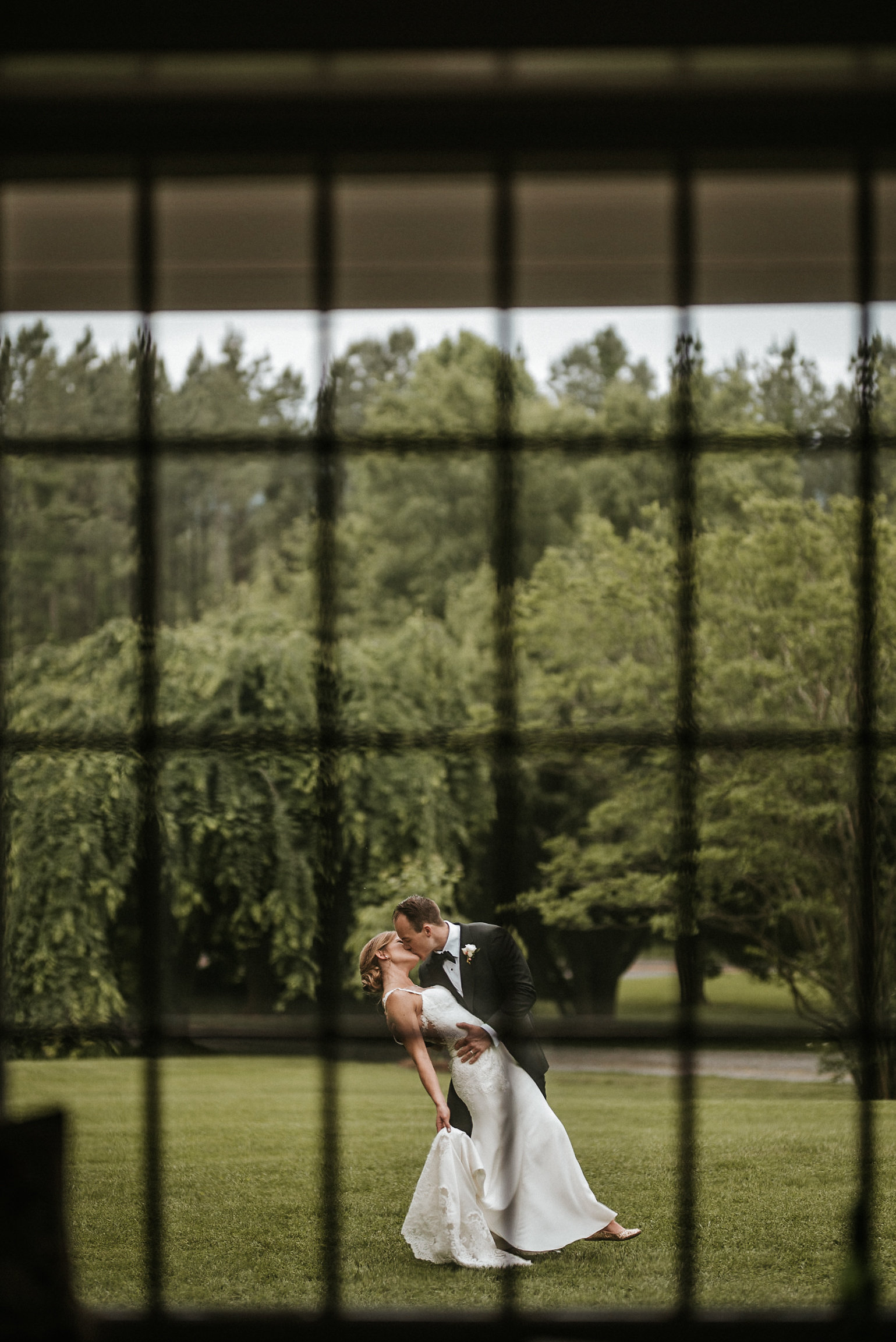 Bride and groom kissing outside window