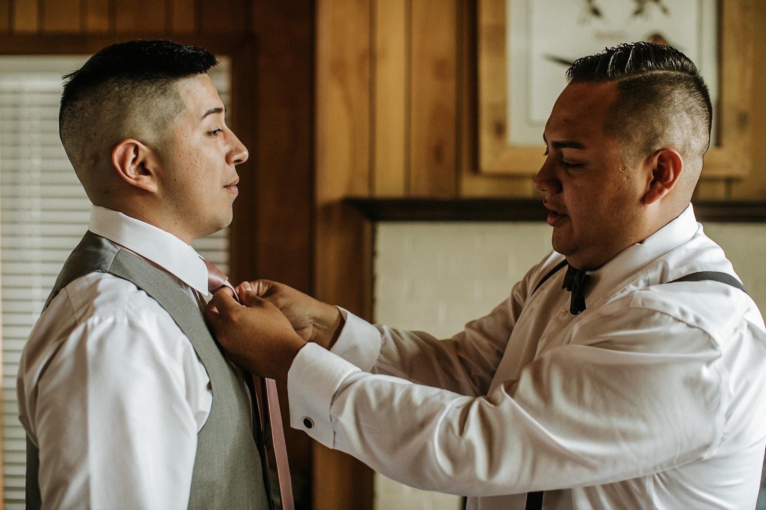 Groom straightening groomsmen's tie