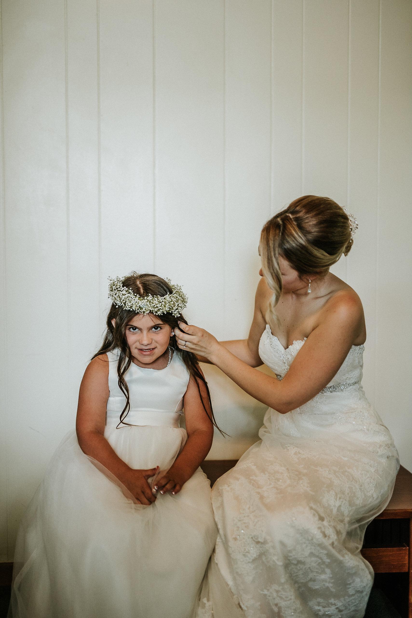 Bride helping flower girl