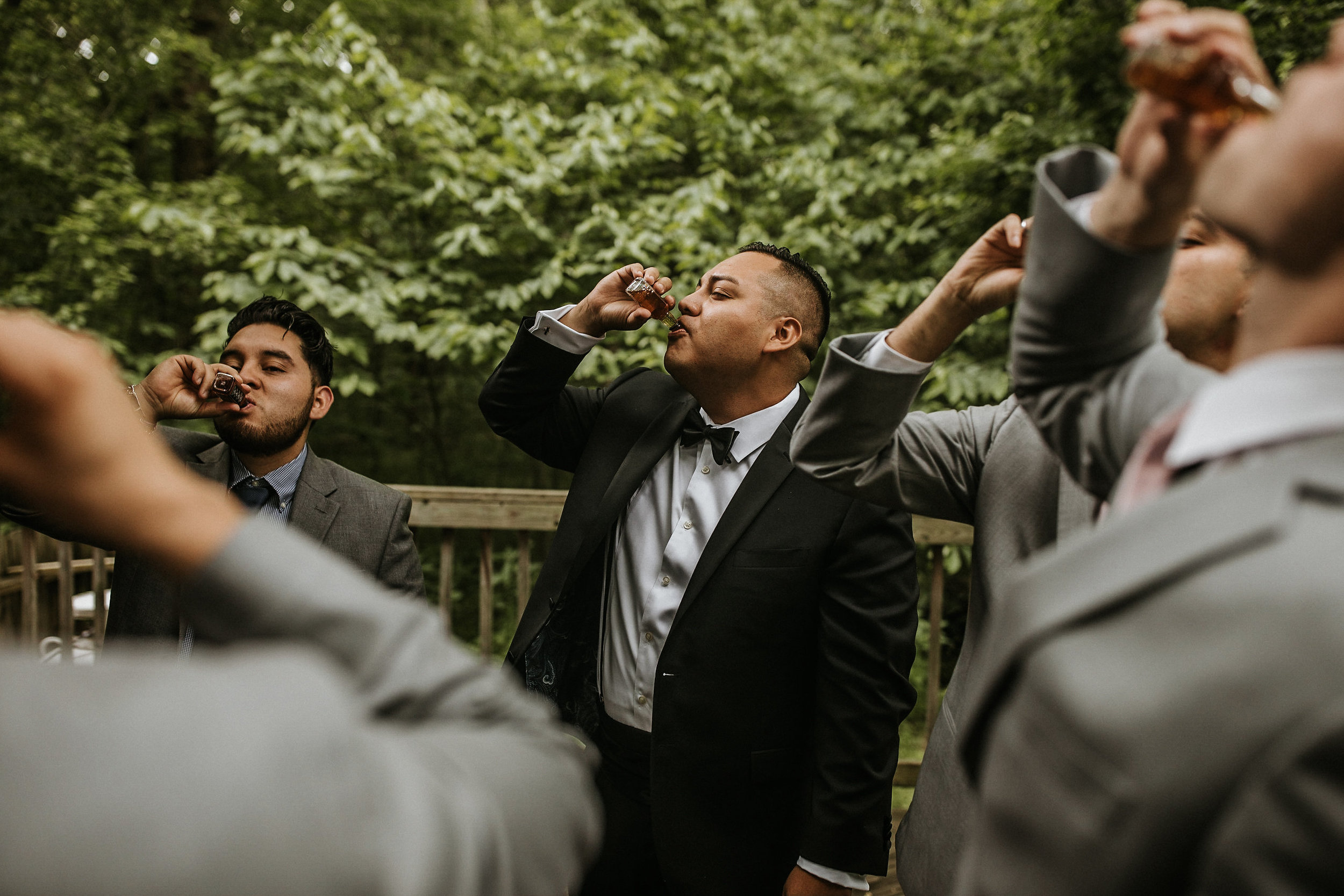 Grooms share shots before wedding