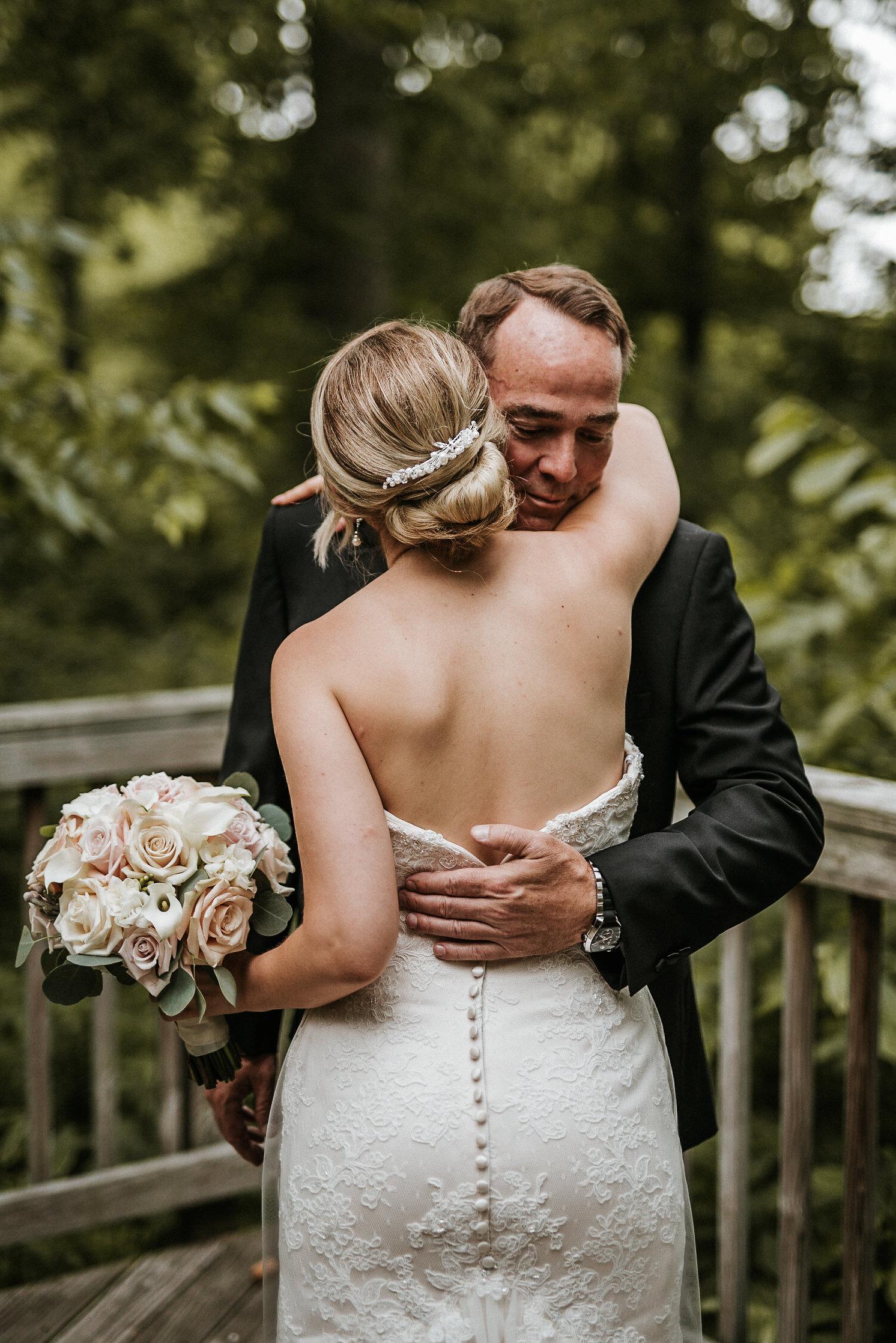 Father and bride hugging during first look