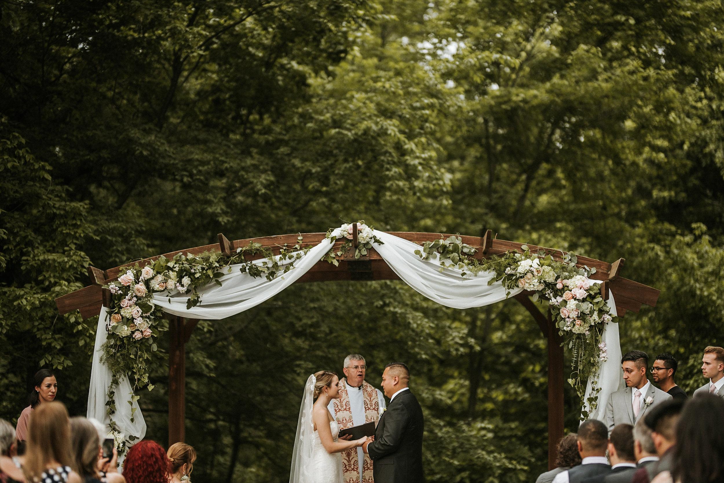Bride and groom under pergola in woods
