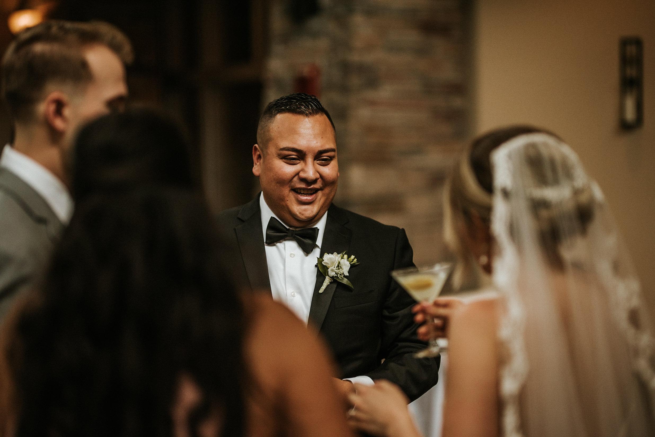 Groom talking to wedding guests