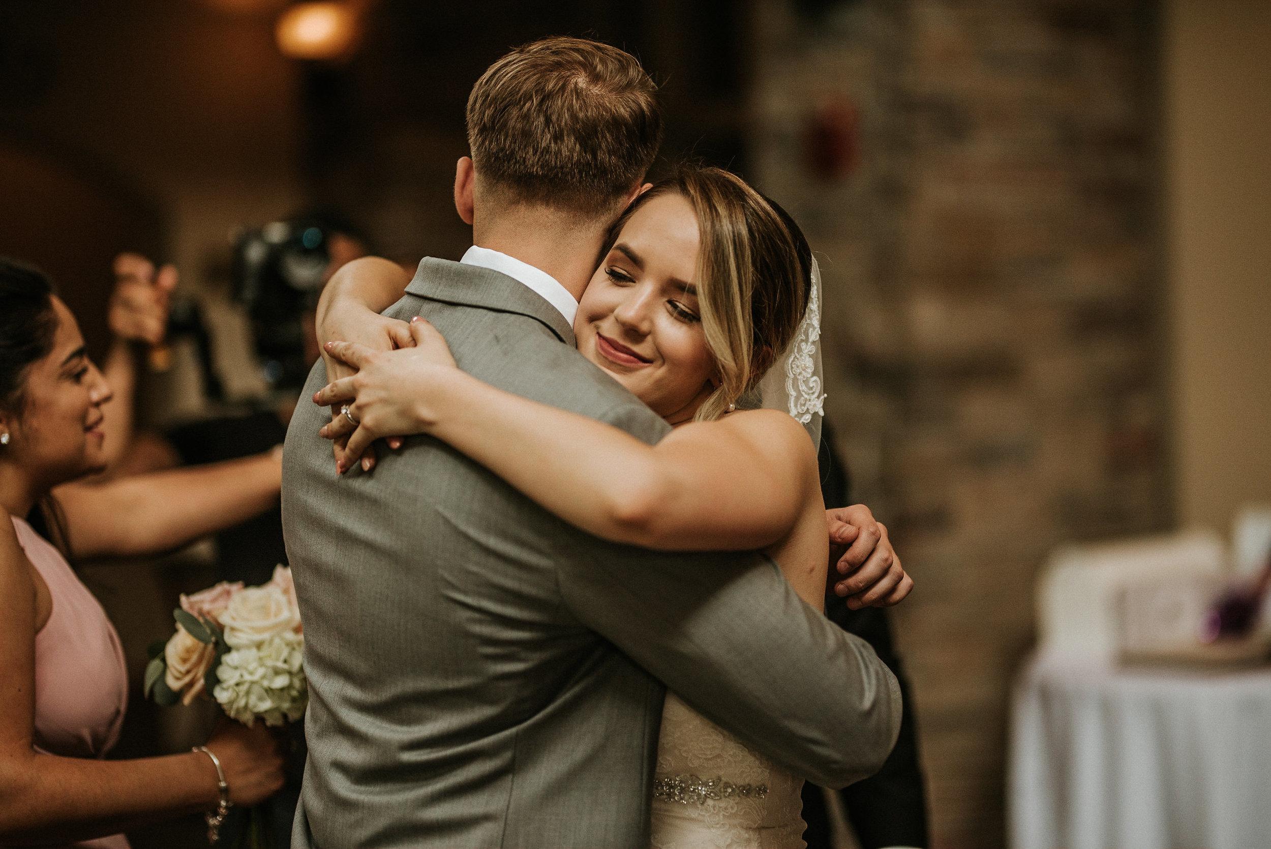 Bride hugging groomsman