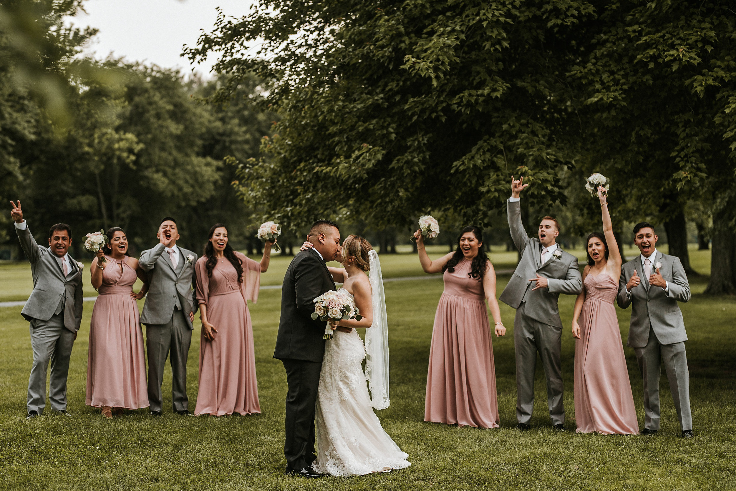 Bridal party cheering as couple kisses